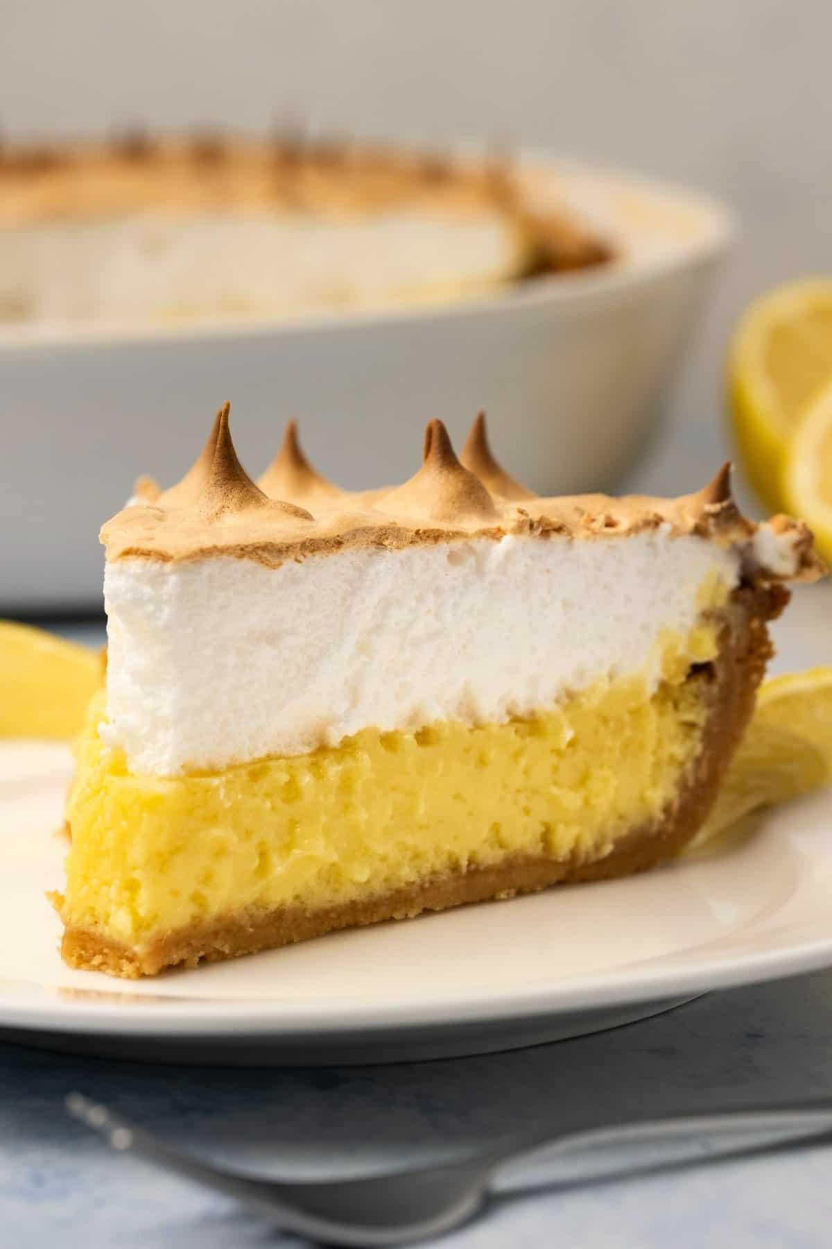 Slice of lemon meringue pie on a white plate.