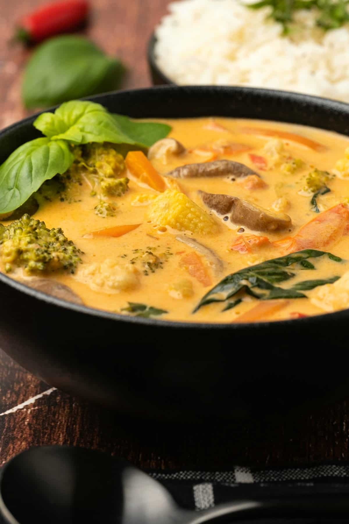 Thai red curry with fresh basil in a black bowl.