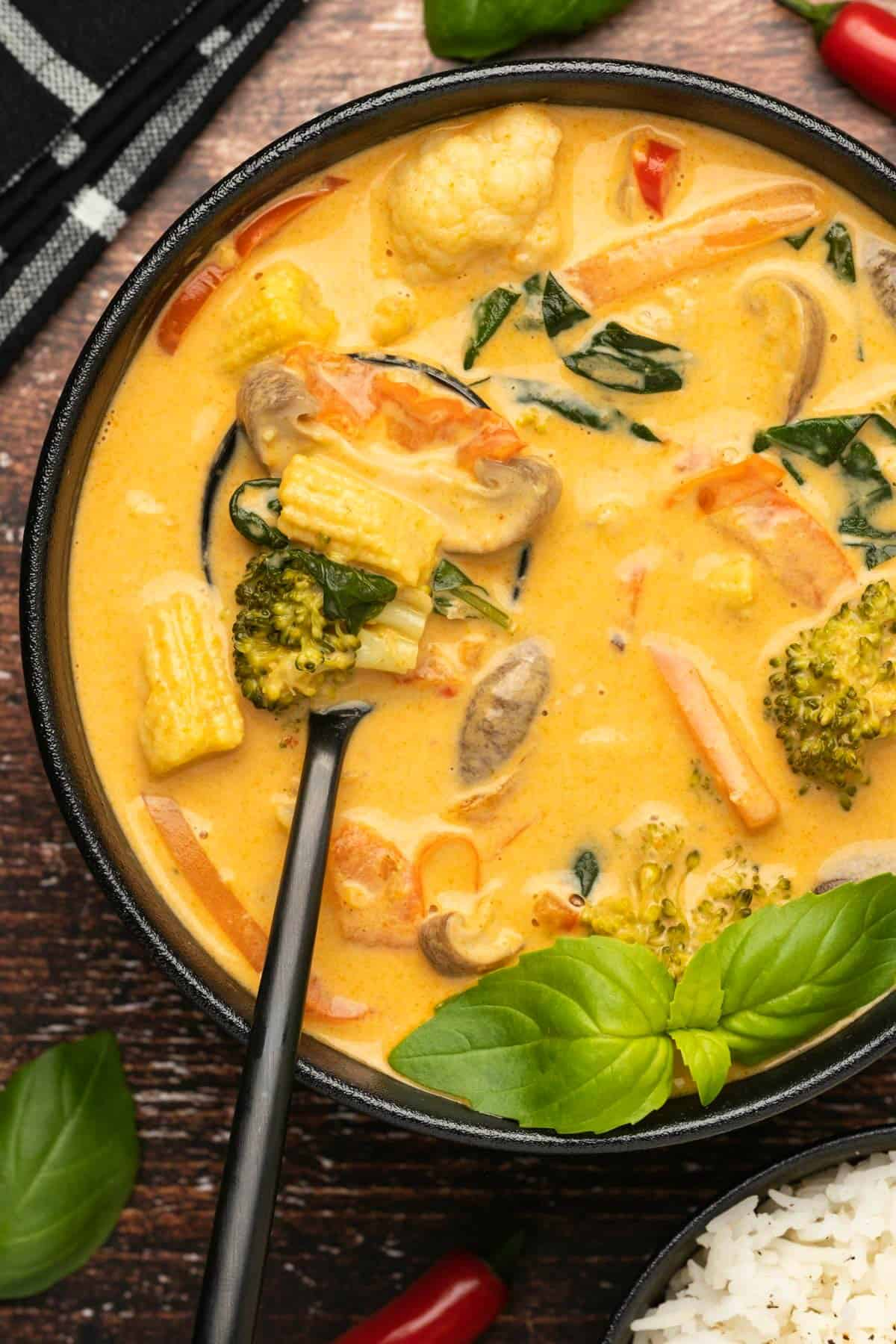 Thai red curry with fresh basil in a bowl with a spoon.