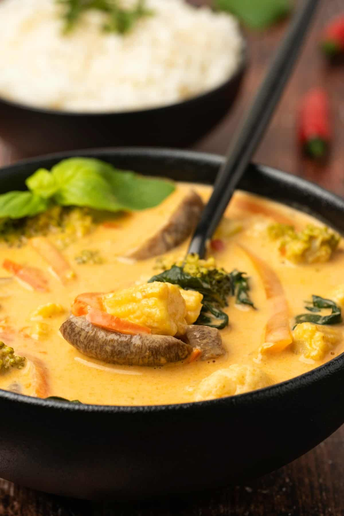 A bowl of red curry and vegetables with a spoon.