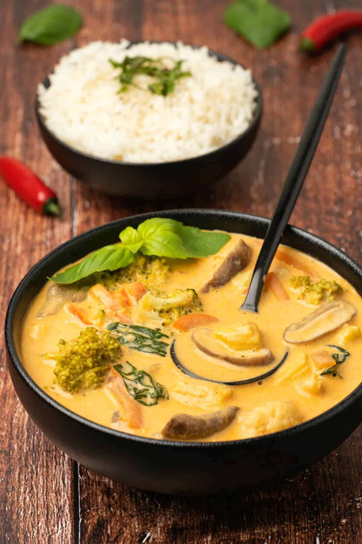 Thai red curry in a black bowl with a spoon.