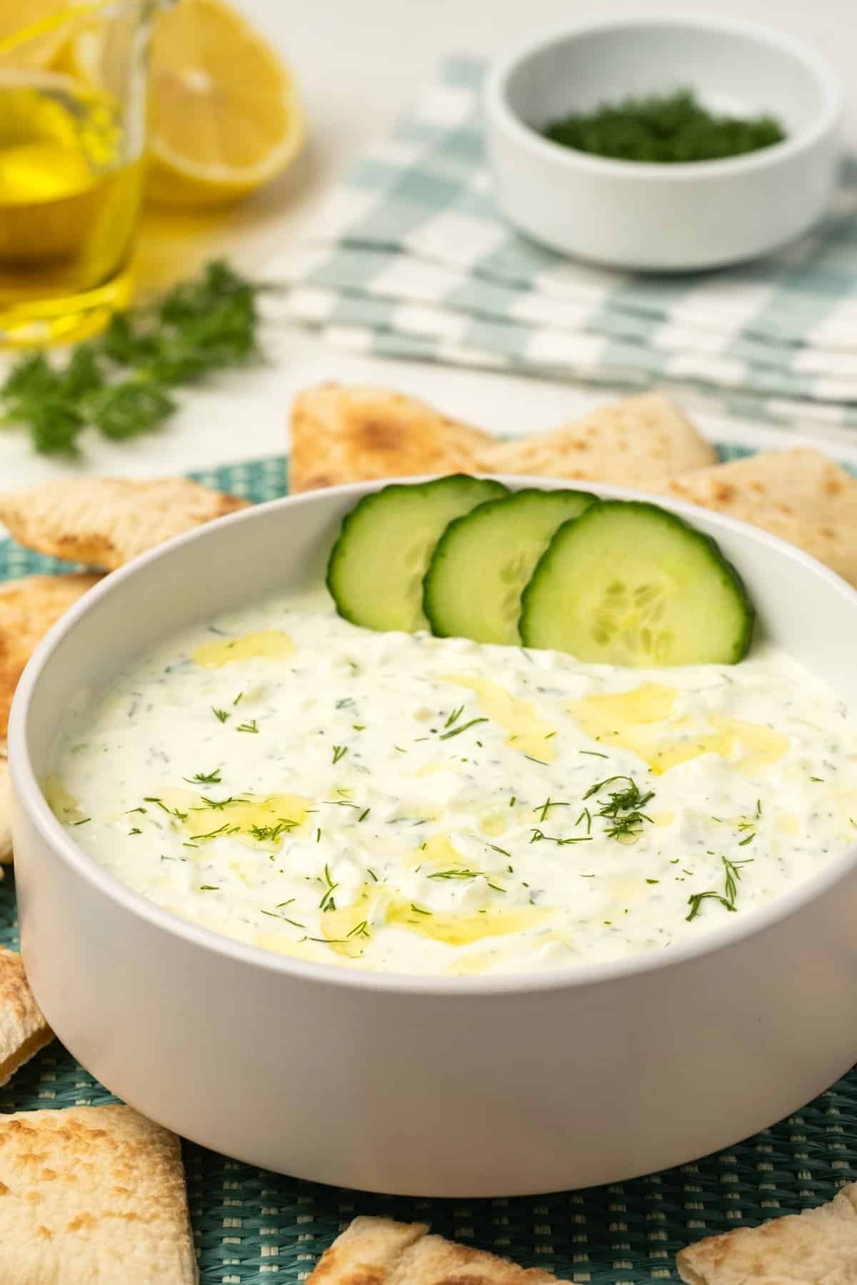 Tzatziki topped with olive oil, fresh dill and cucumber slices in a white bowl.