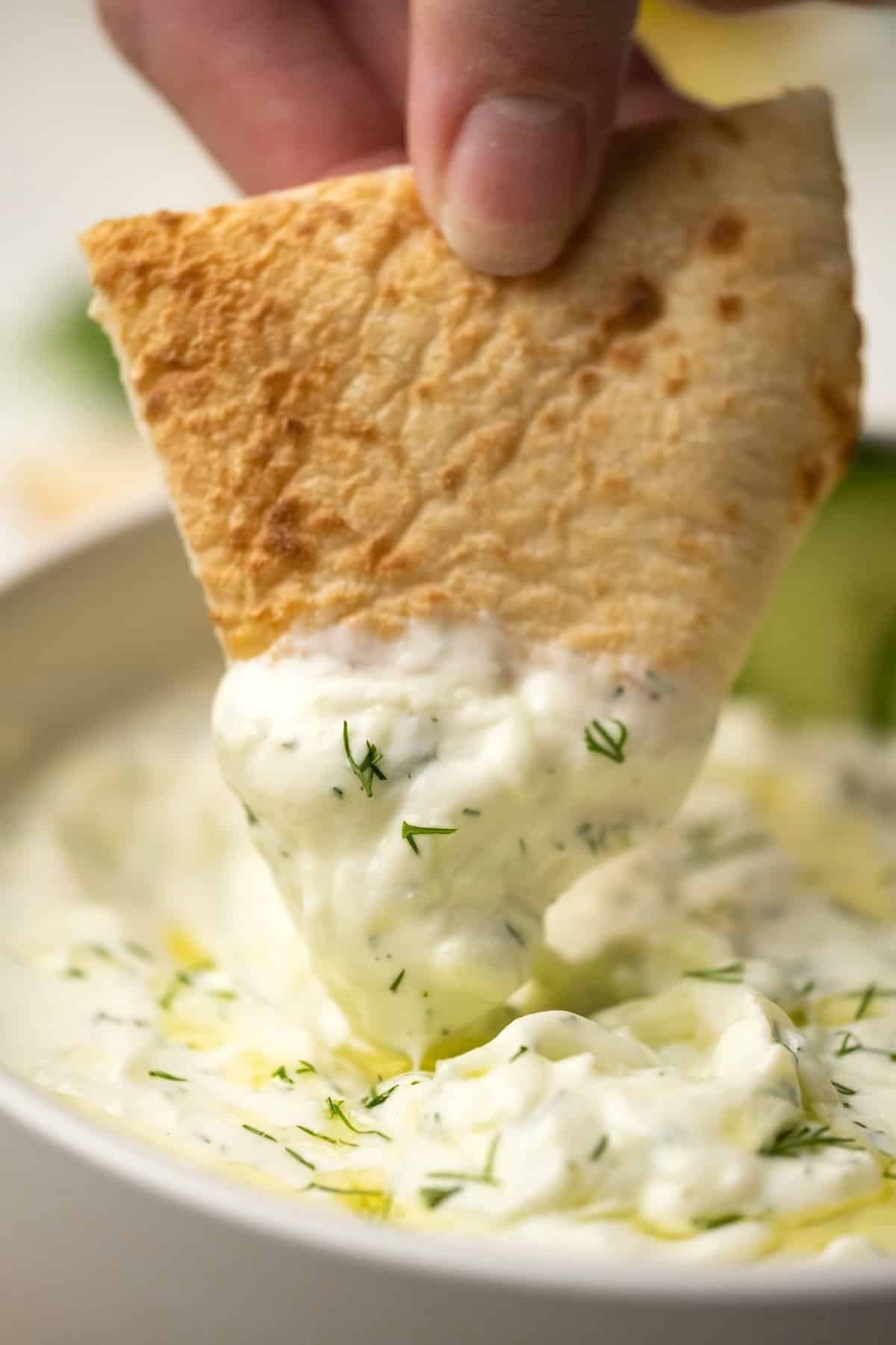 Pita bread dipping into a bowl of tzatziki.