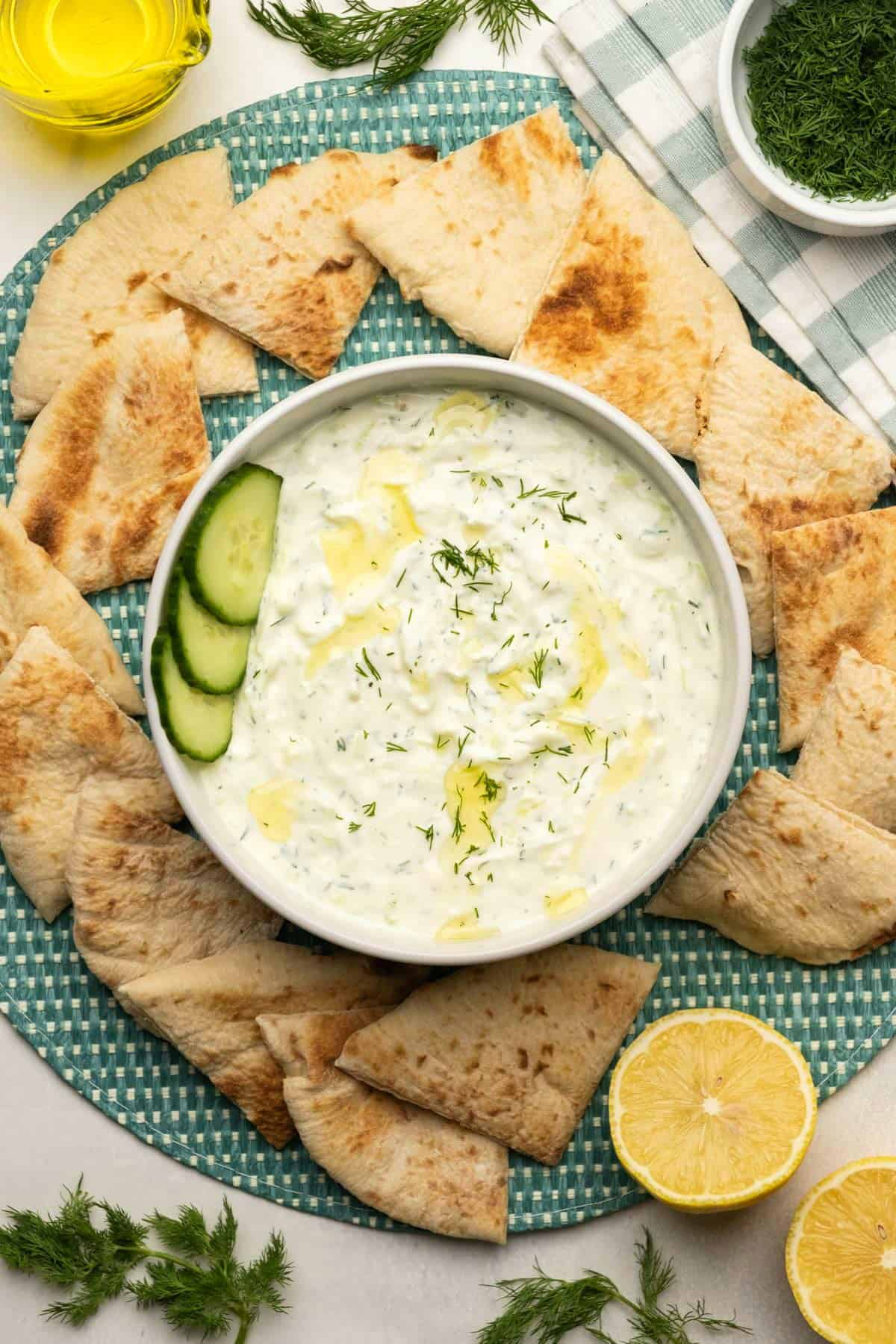 Tzatziki topped with olive oil and fresh dill in a white bowl.