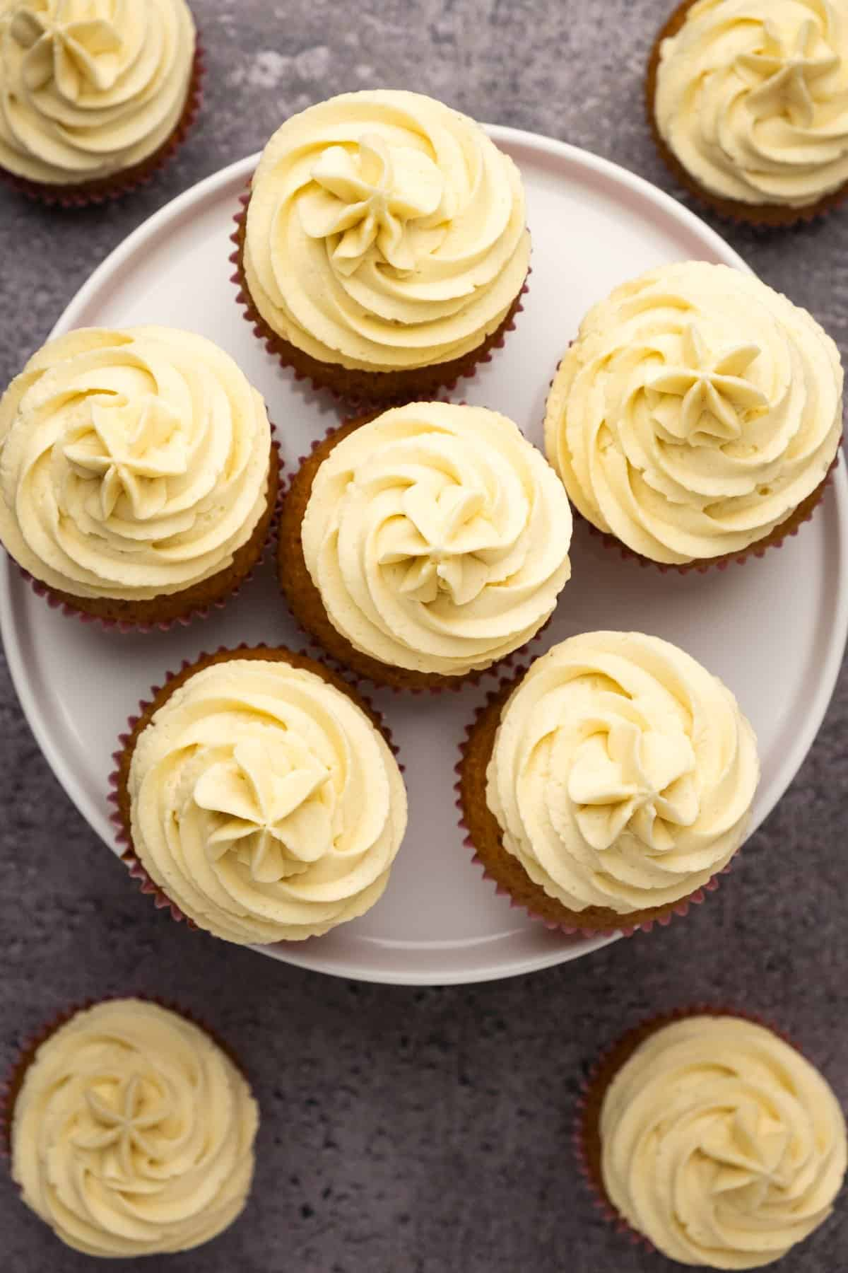 Cupcakes with frosting on a white cake stand.