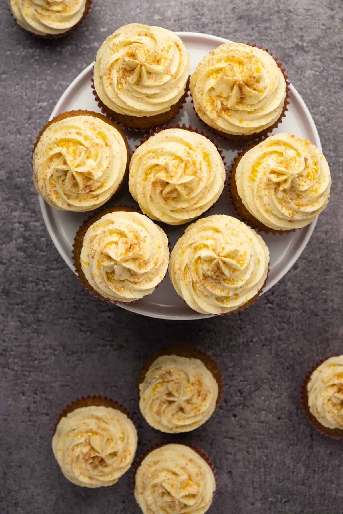 Cupcakes topped with vanilla frosting and gold decoration on a white cake stand.
