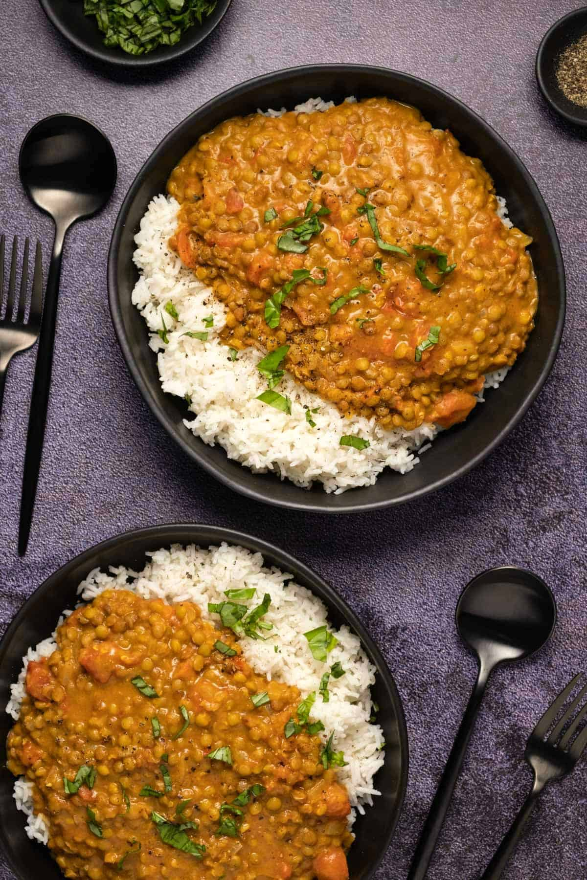 Lentil curry with rice in a black bowl.