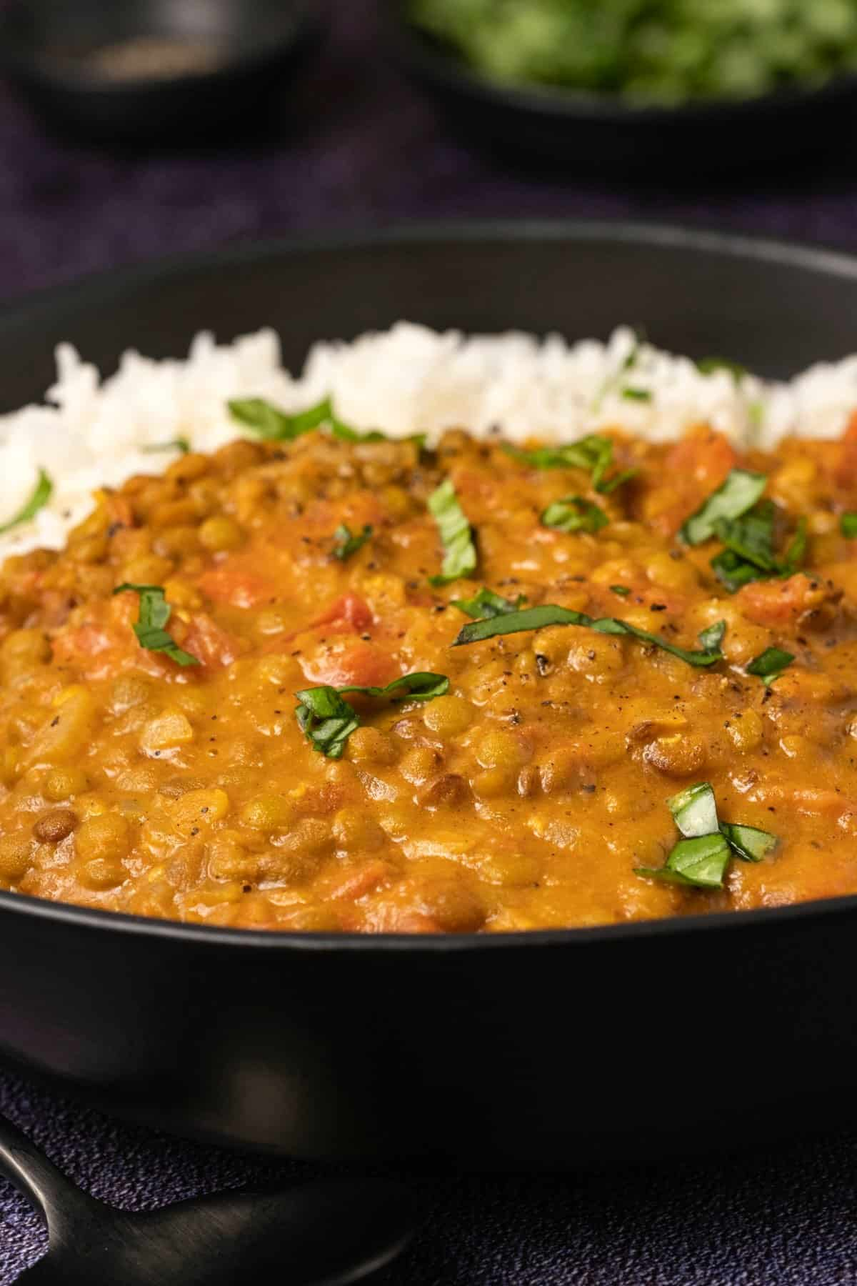 Lentil curry with rice and chopped basil in a black bowl.
