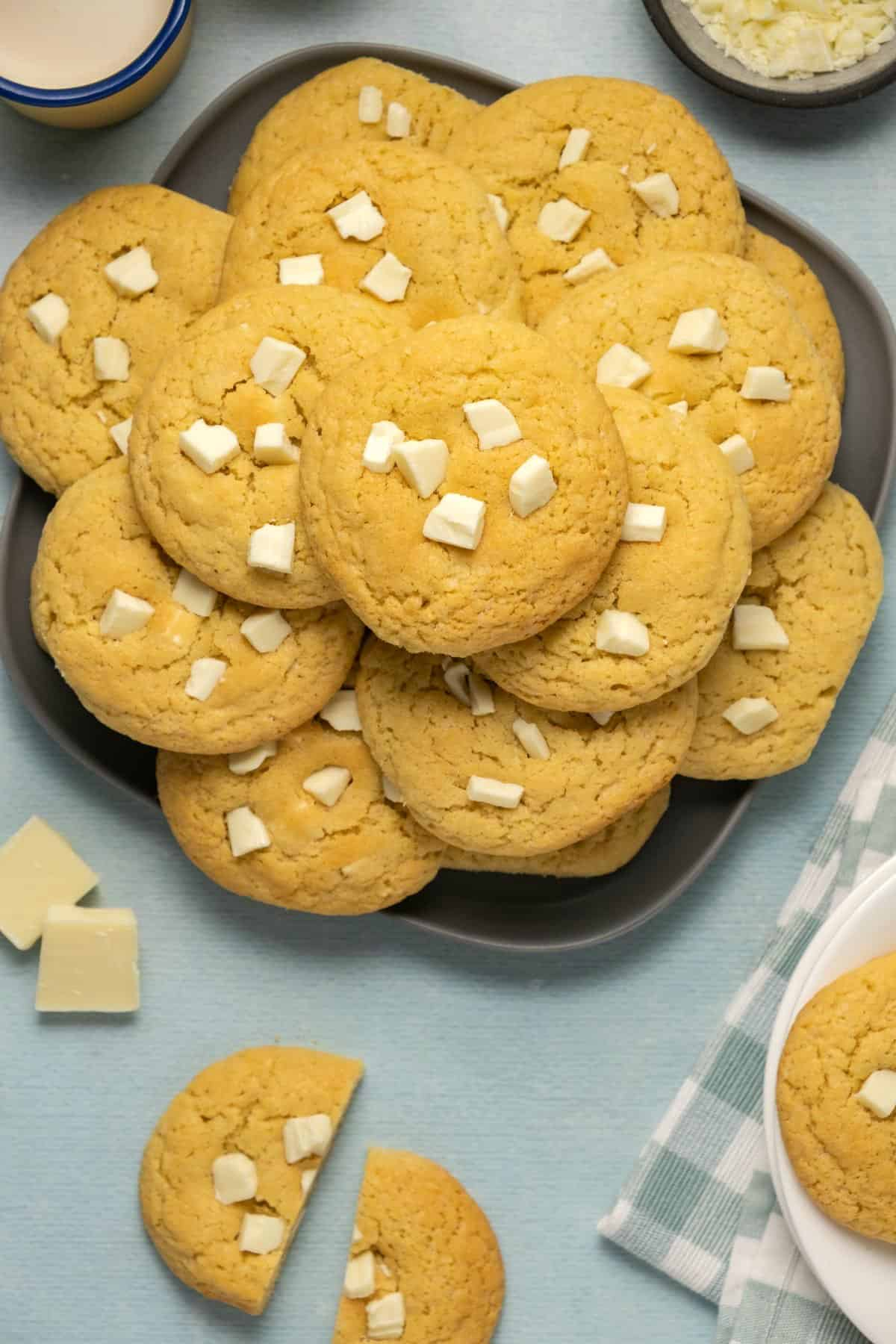 White chocolate chip cookies stacked up on a plate.