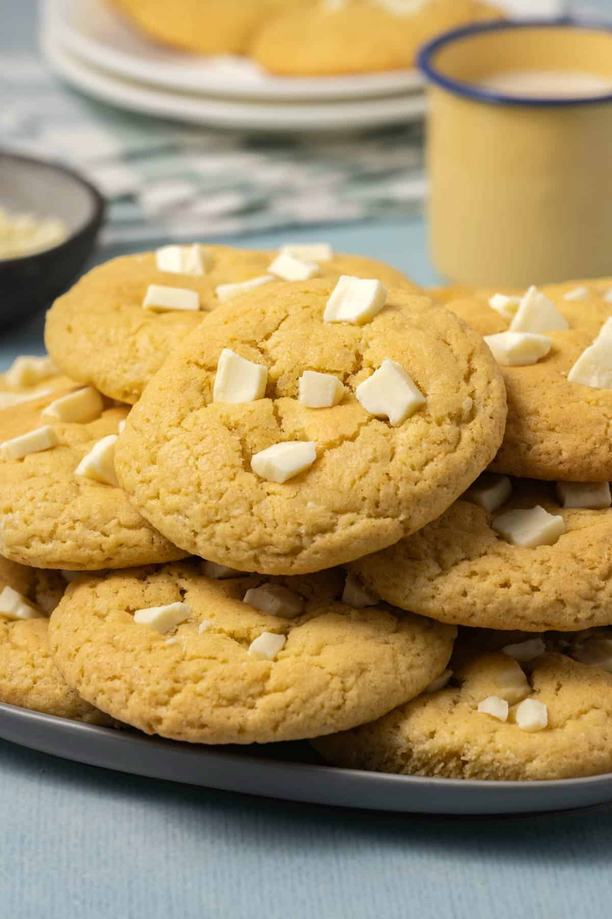 White chocolate chip cookies stacked on a plate.