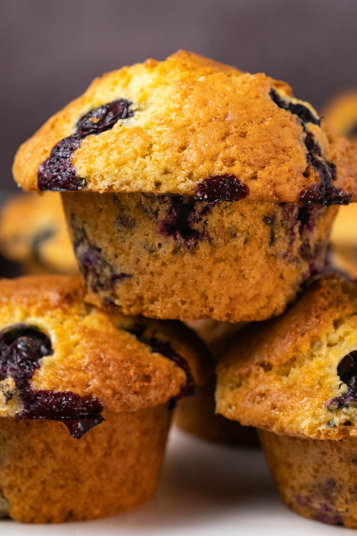 Blueberry muffins stacked up on a white plate.