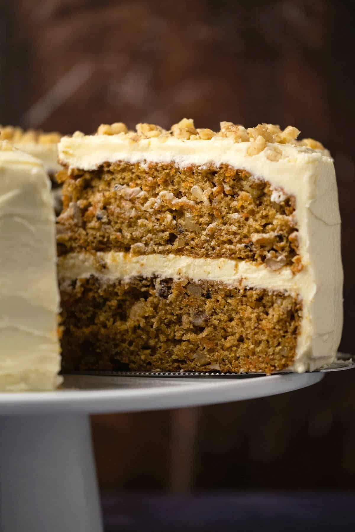 Carrot cake on a white cake stand with one slice cut and ready to serve.