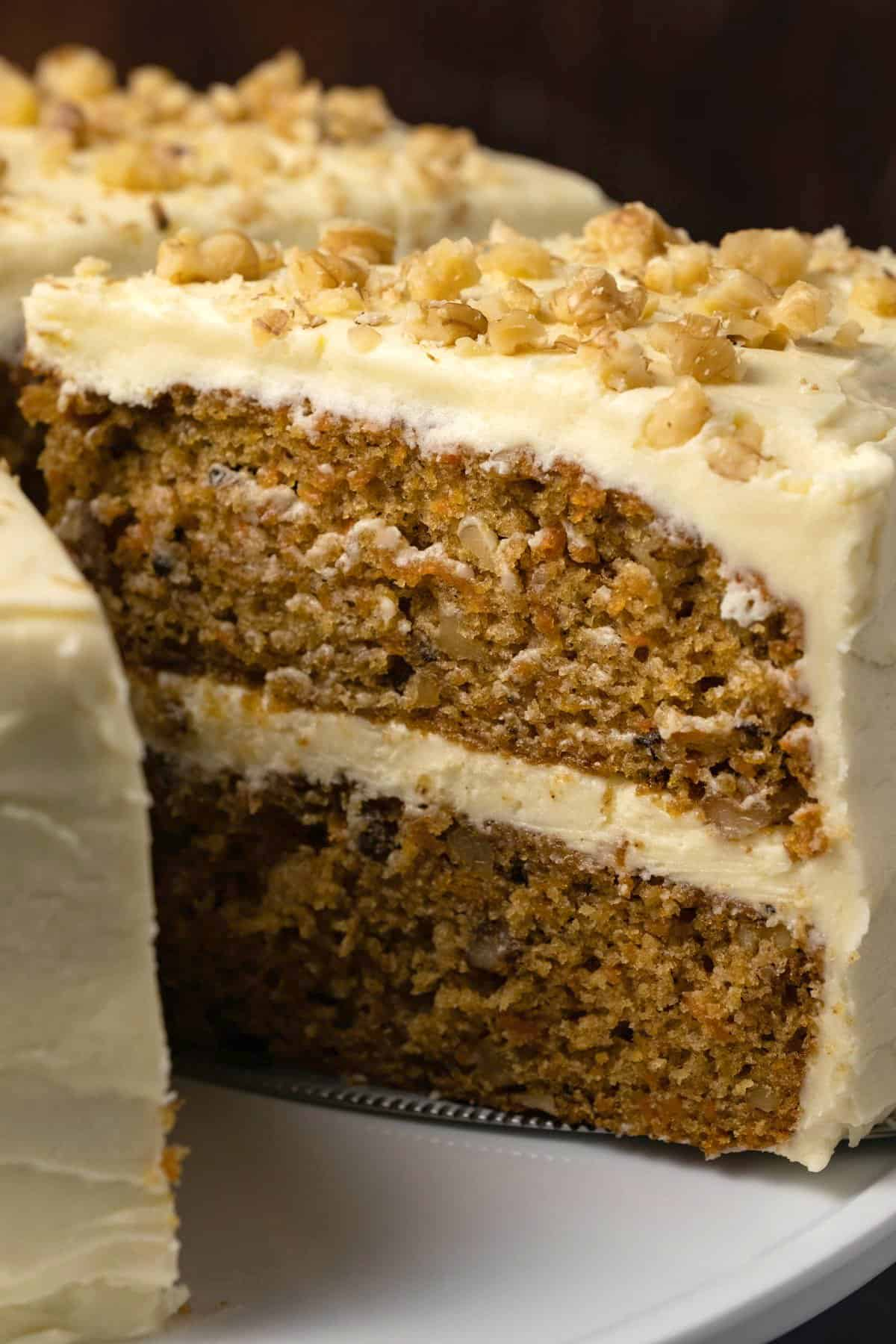 Carrot cake on a cake stand with one slice cut and ready to serve.