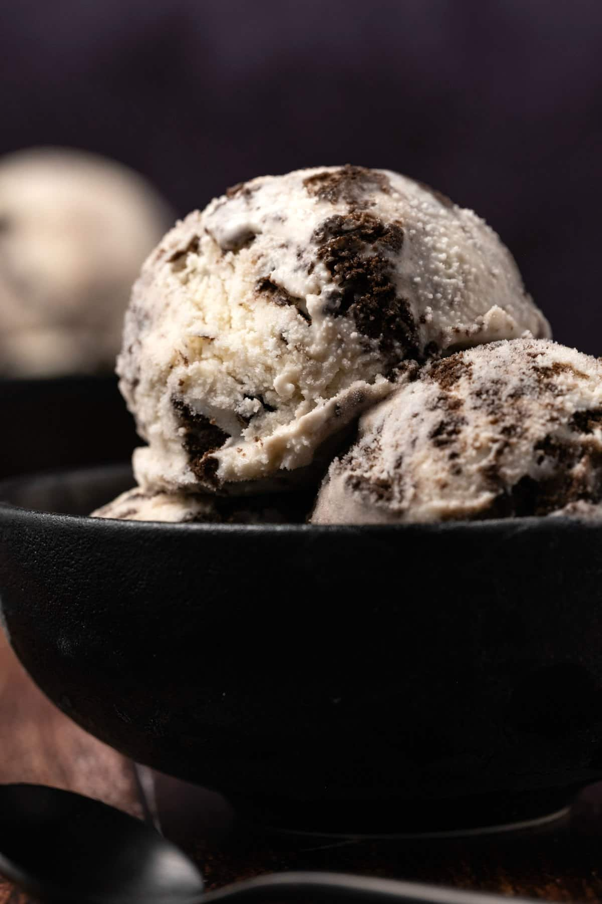 Scoops of cookies and cream ice cream in a black bowl.