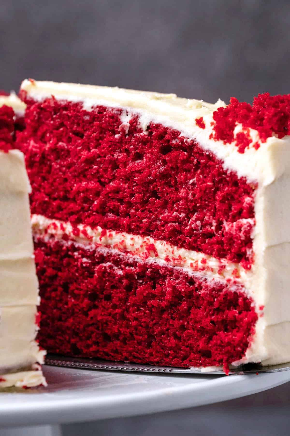 Red velvet cake with one slice cut on a white cake stand.