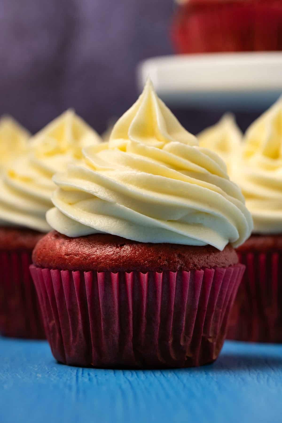 Red velvet cupcakes topped with cream cheese frosting.