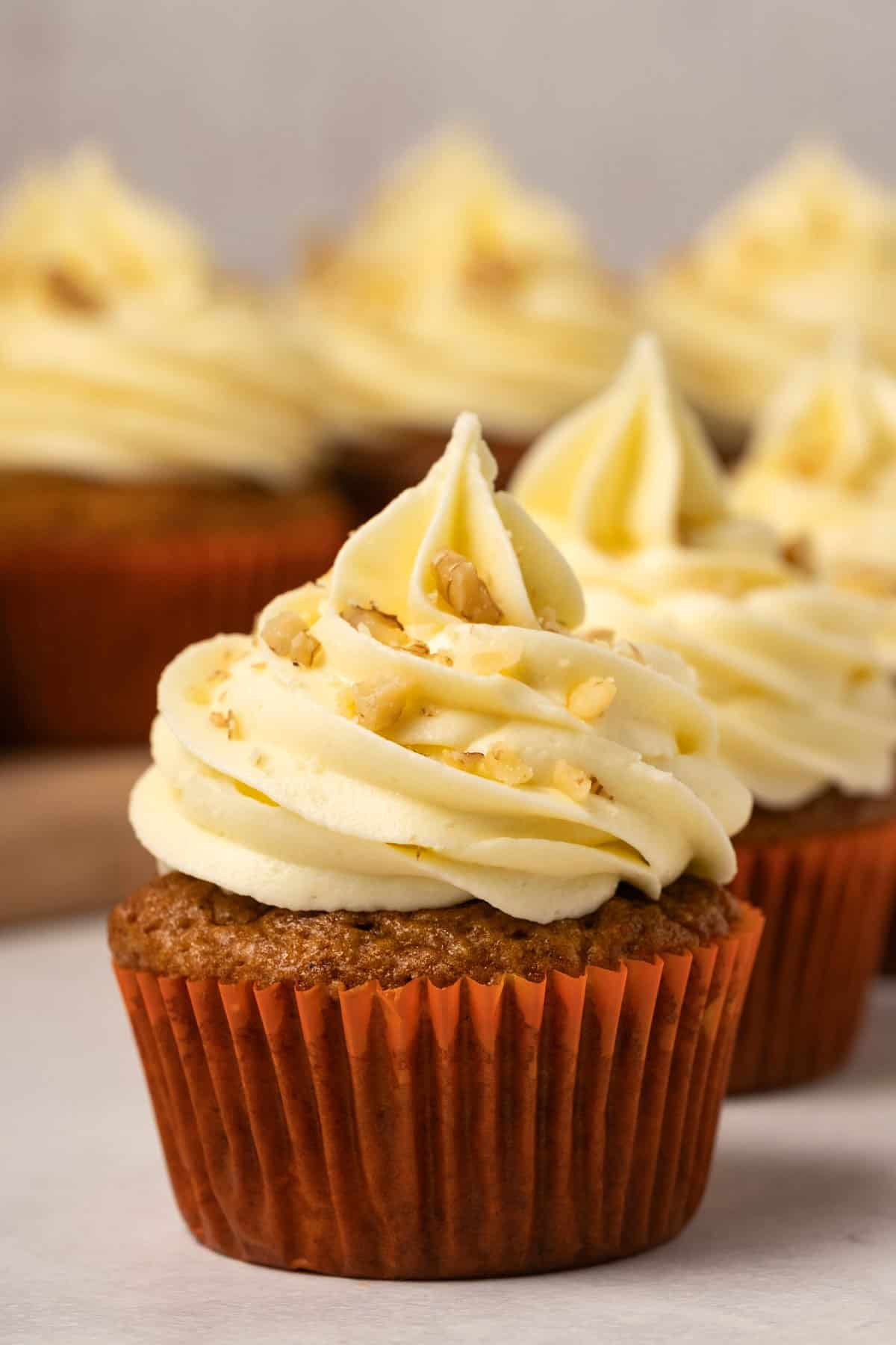 Cupcakes with piped frosting and chopped nuts.