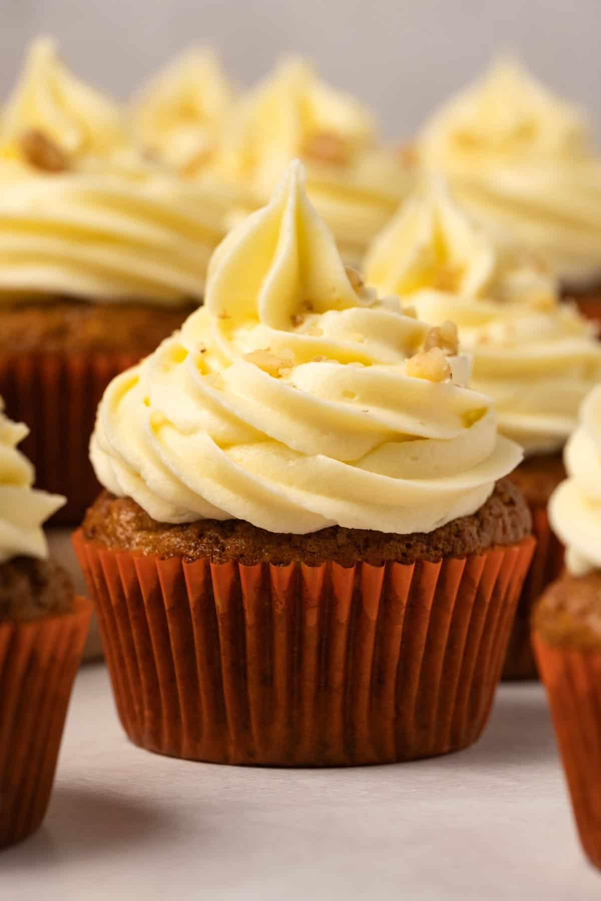 Cupcakes topped with piped frosting and chopped nuts.