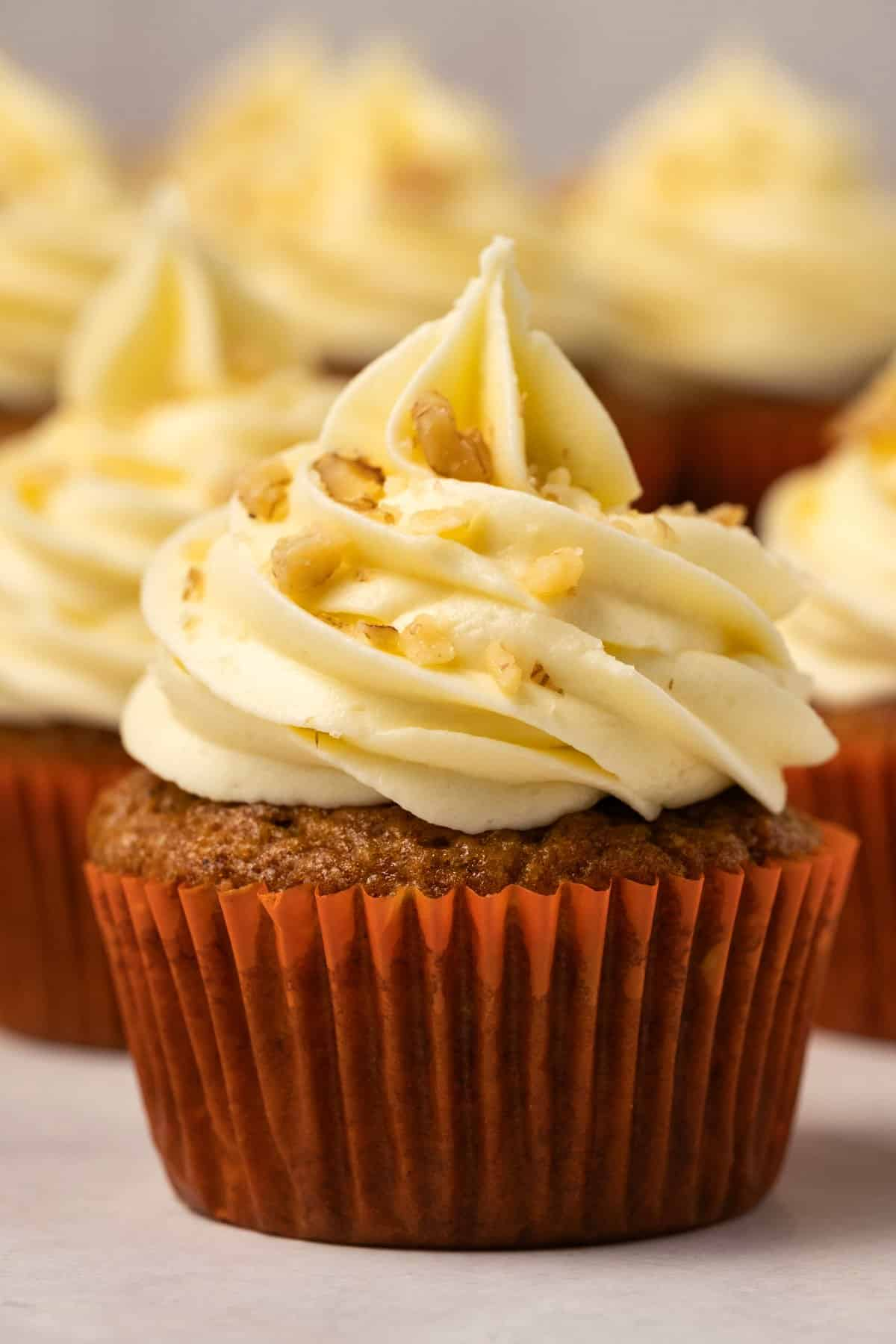 Carrot cake cupcakes topped with cream cheese frosting and chopped walnuts.