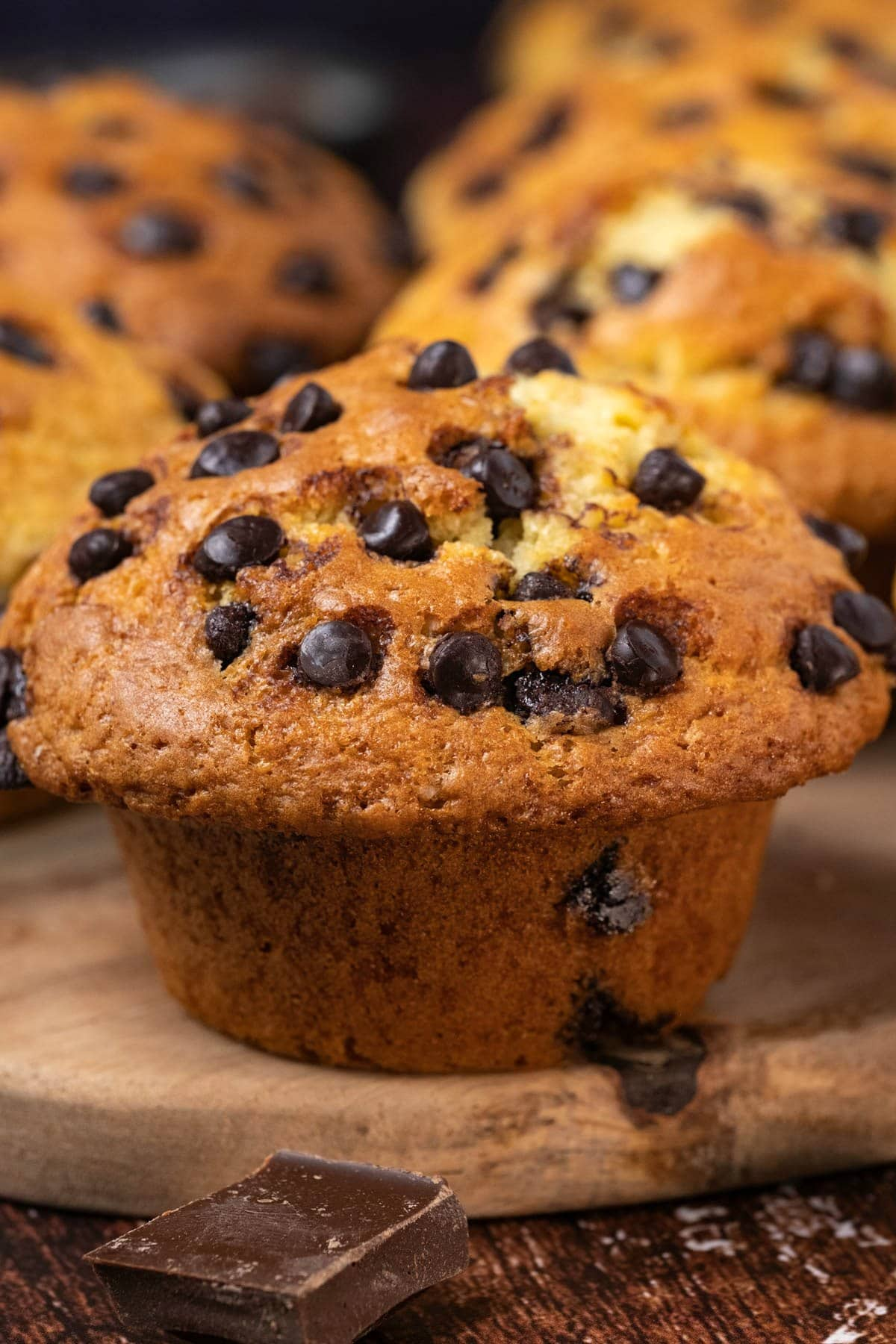 Chocolate chip muffins on a wooden board.