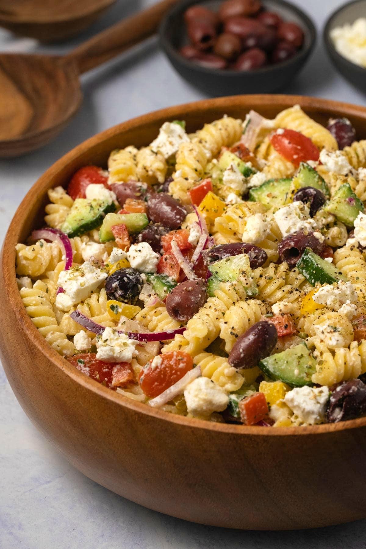 Greek pasta salad in a wooden salad bowl.