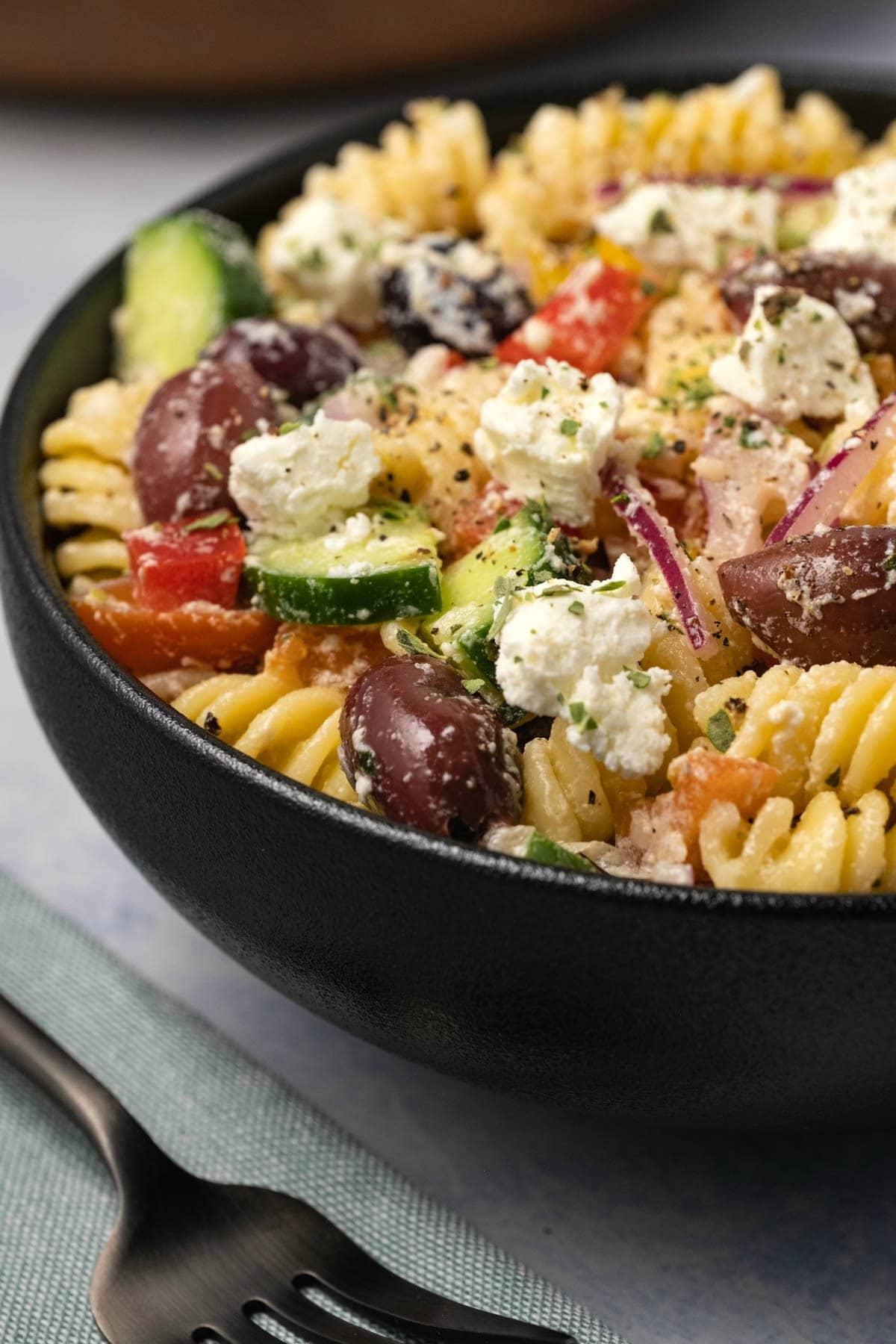 Greek pasta salad in a black bowl.