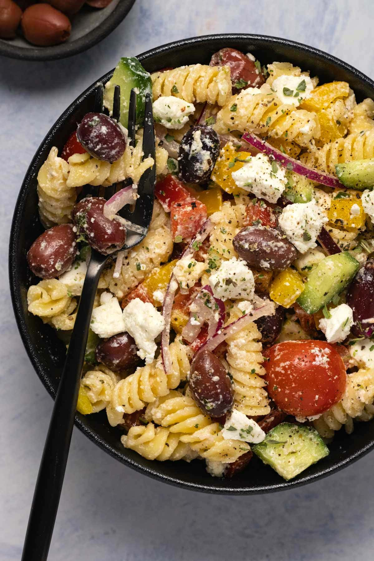 Greek pasta salad in a black bowl with a fork.