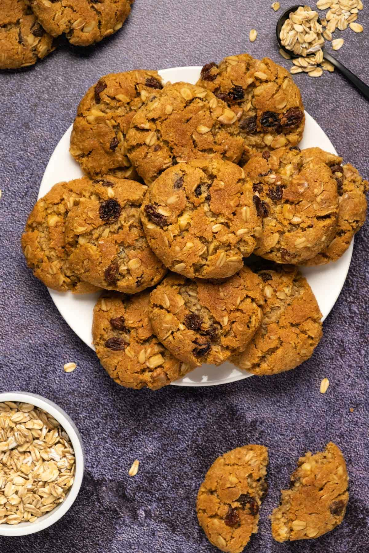 Oatmeal raisin cookies stacked up on a white plate.