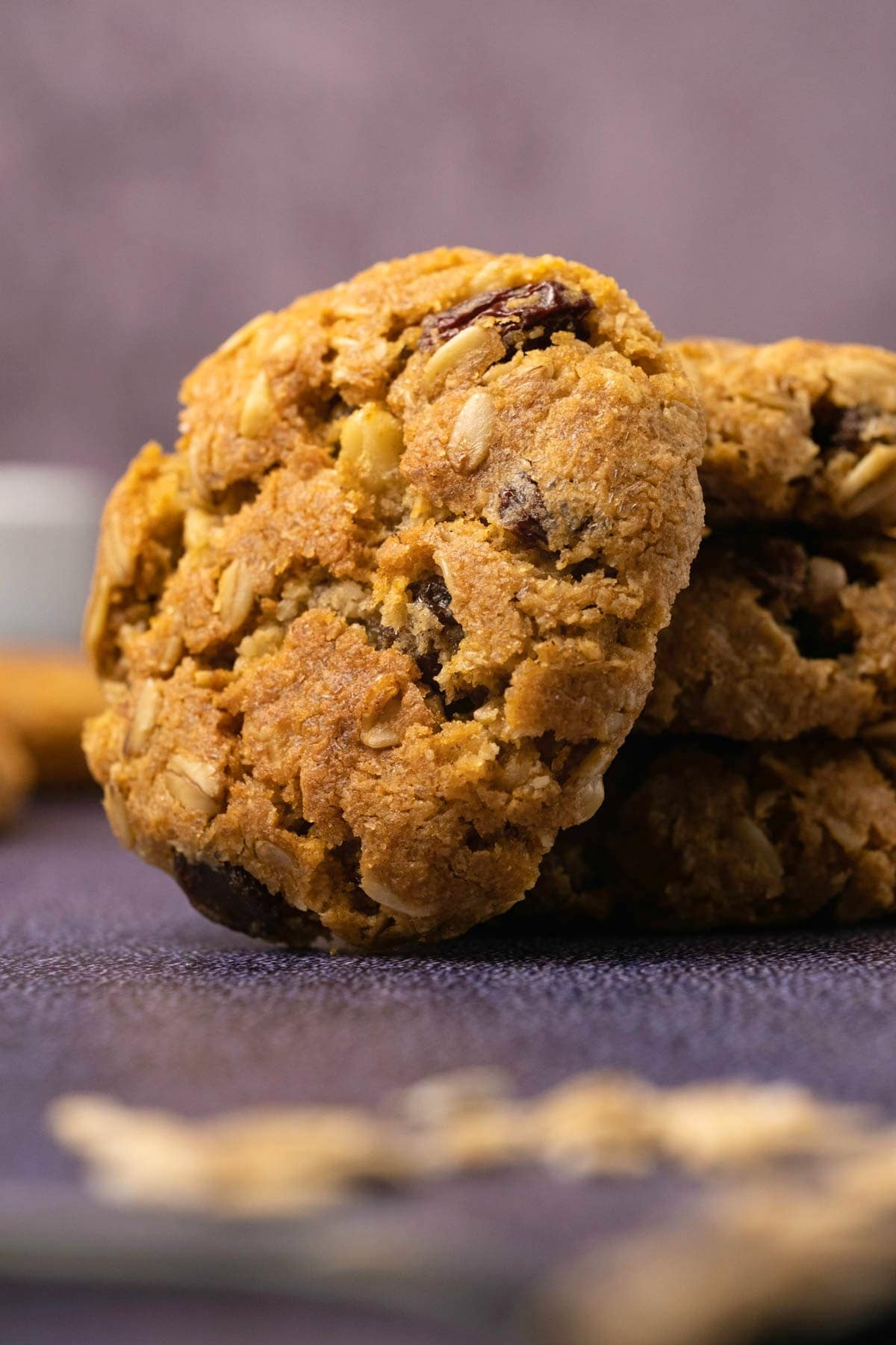 Oatmeal raisin cookie leaning against a stack of three cookies.