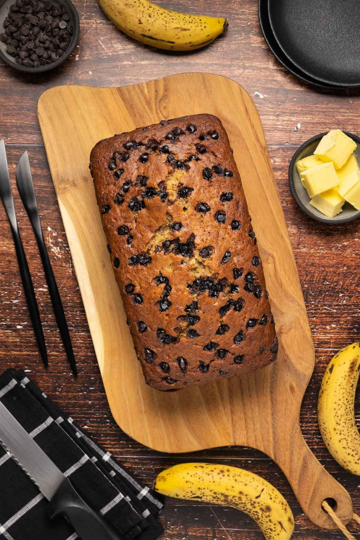 Loaf of chocolate chip banana bread on a wooden board.