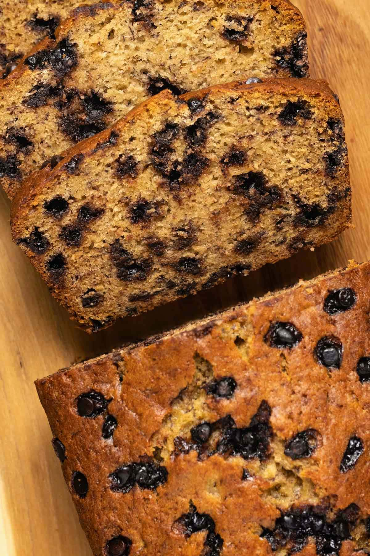 Chocolate chip banana bread with slices cut on a wooden board.