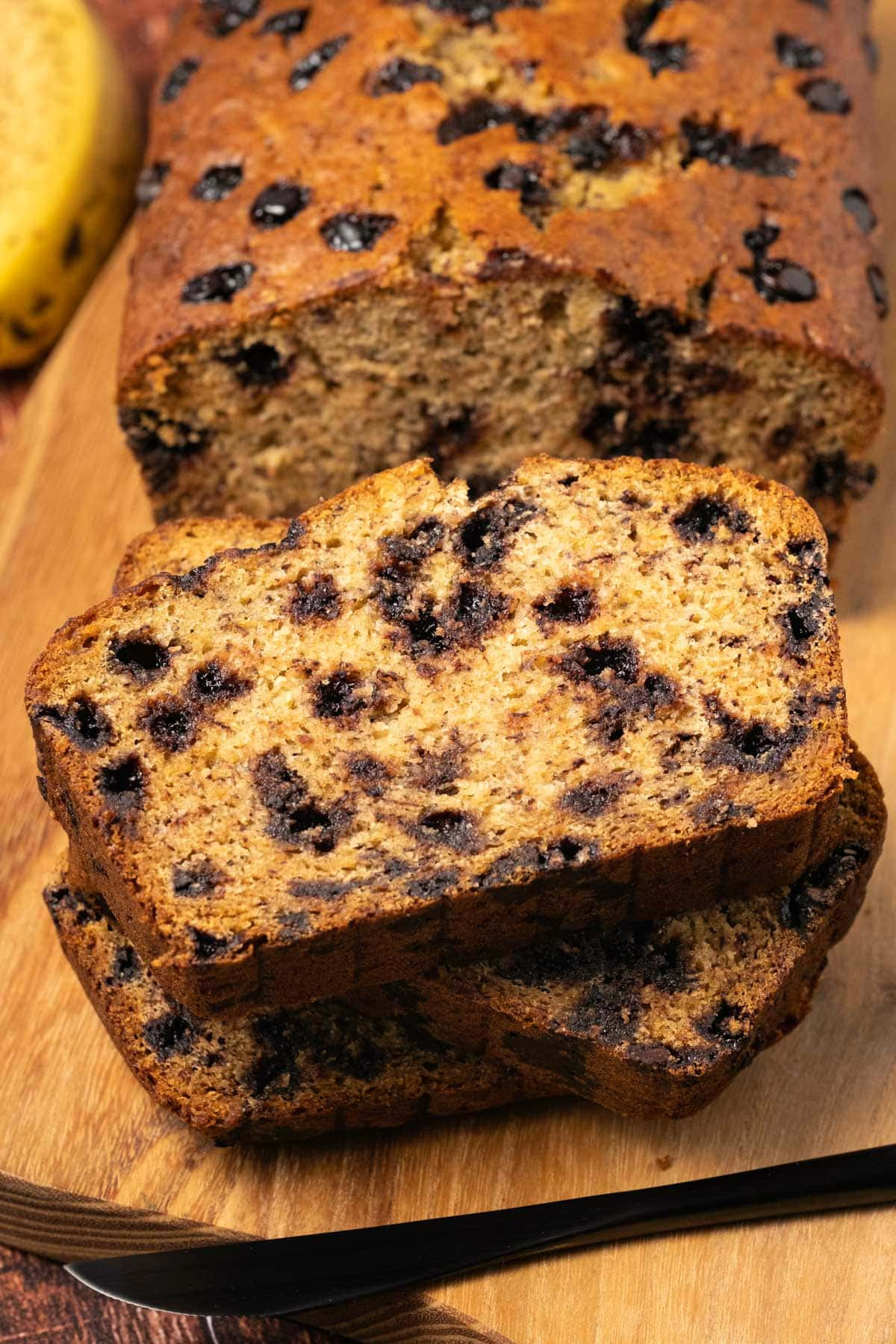 Slices of chocolate chip banana bread on a wooden board.