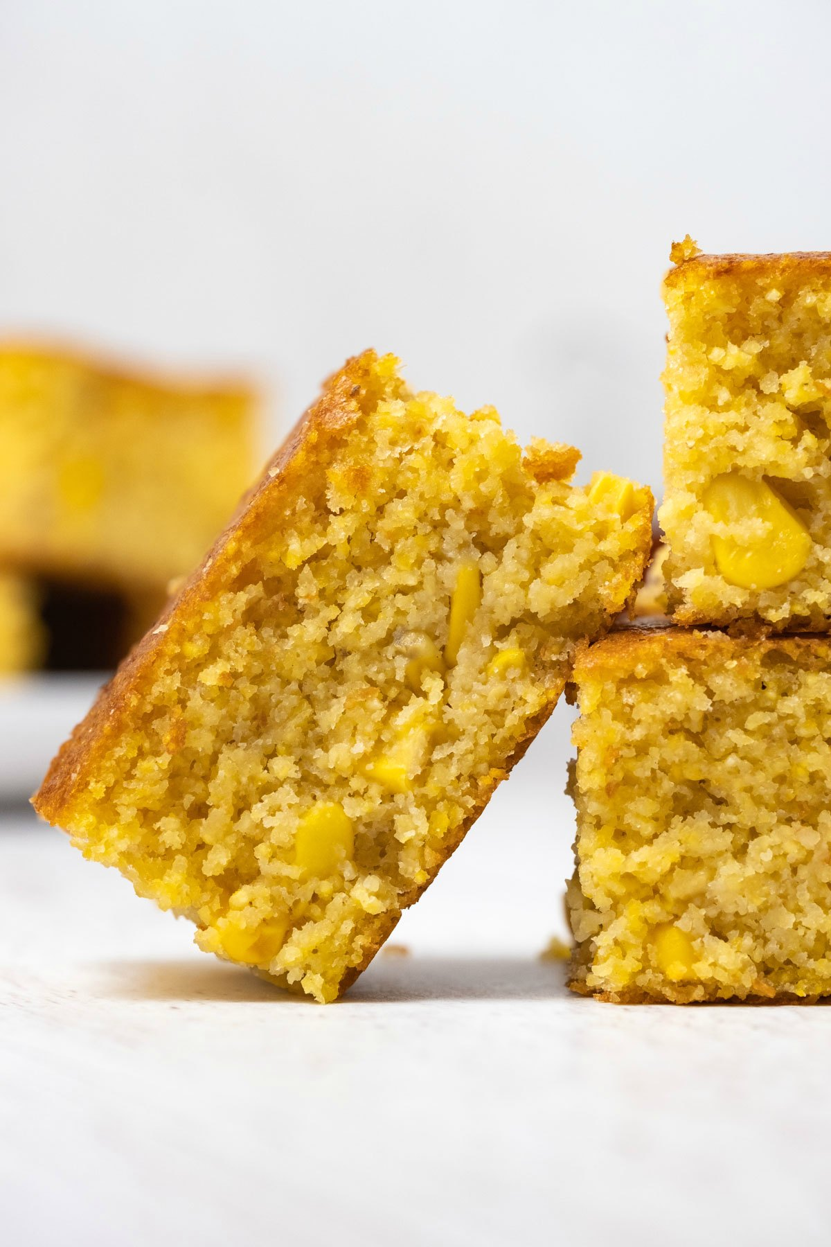 Slice of cornbread leaning against cornbread in a stack.