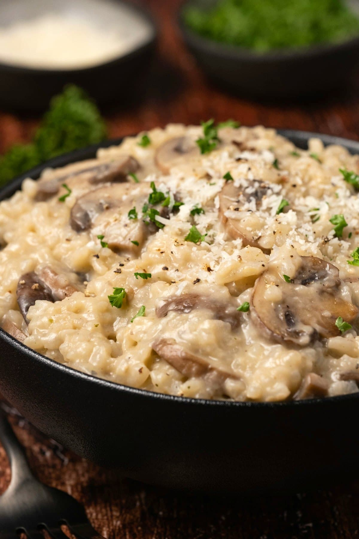 Risotto topped with grated parmesan in a black bowl.