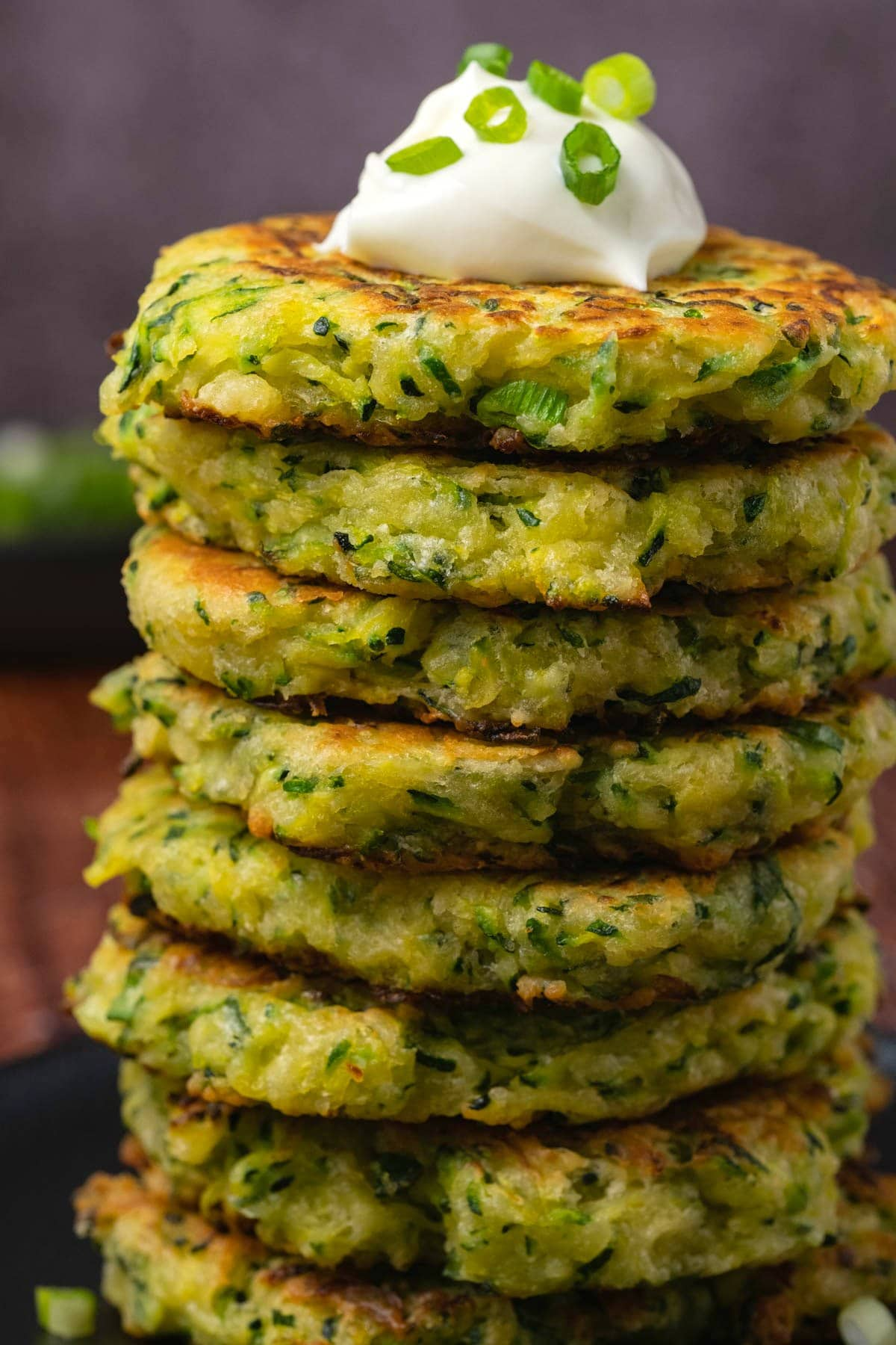Stack of zucchini fritters topped with Greek yogurt on a black plate.