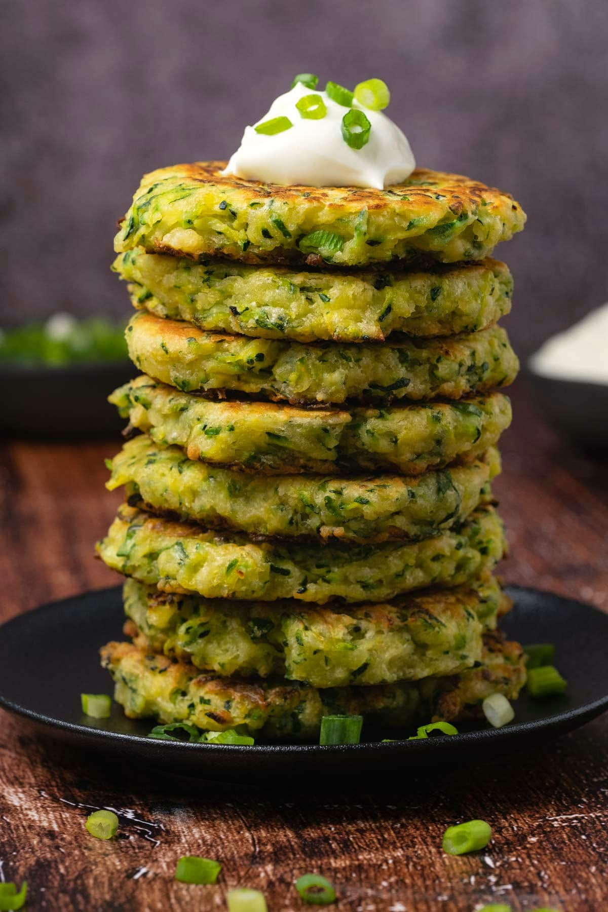 Zucchini fritters in a stack topped with Greek yogurt and chopped green onions.