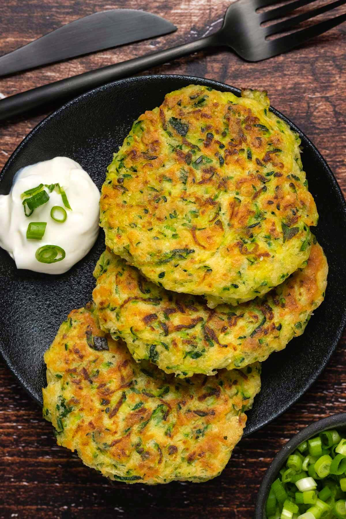 Zucchini fritters on a black plate.