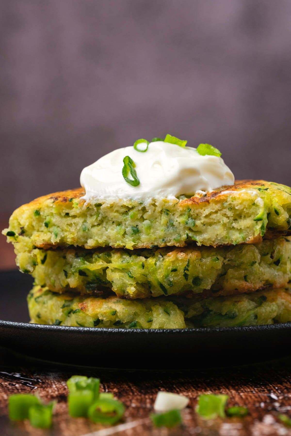 Zucchini fritters in a stack with the top fritter sliced in half.