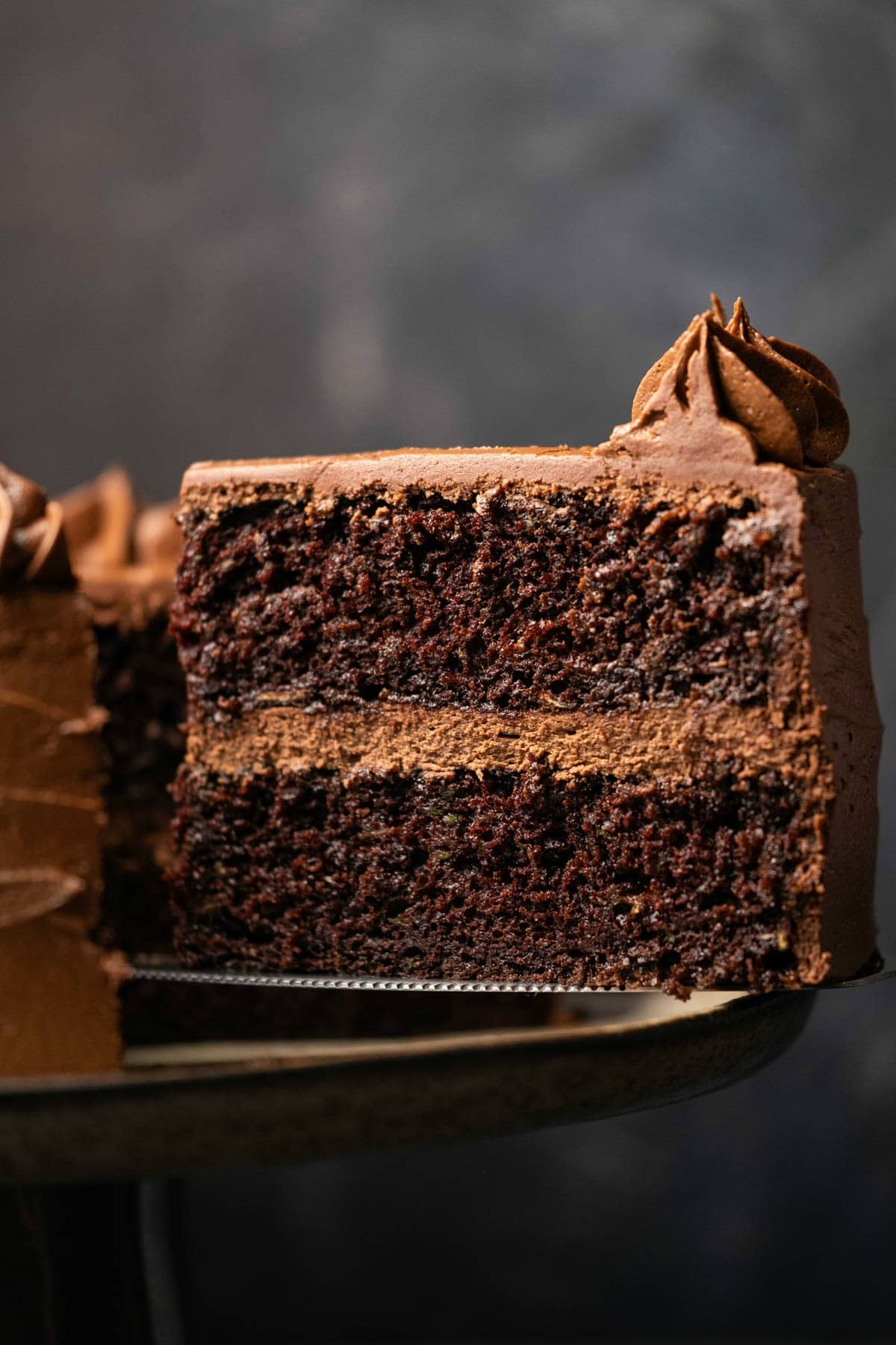 Chocolate zucchini cake on a cake stand with one slice cut and ready to serve on a cake lifter.