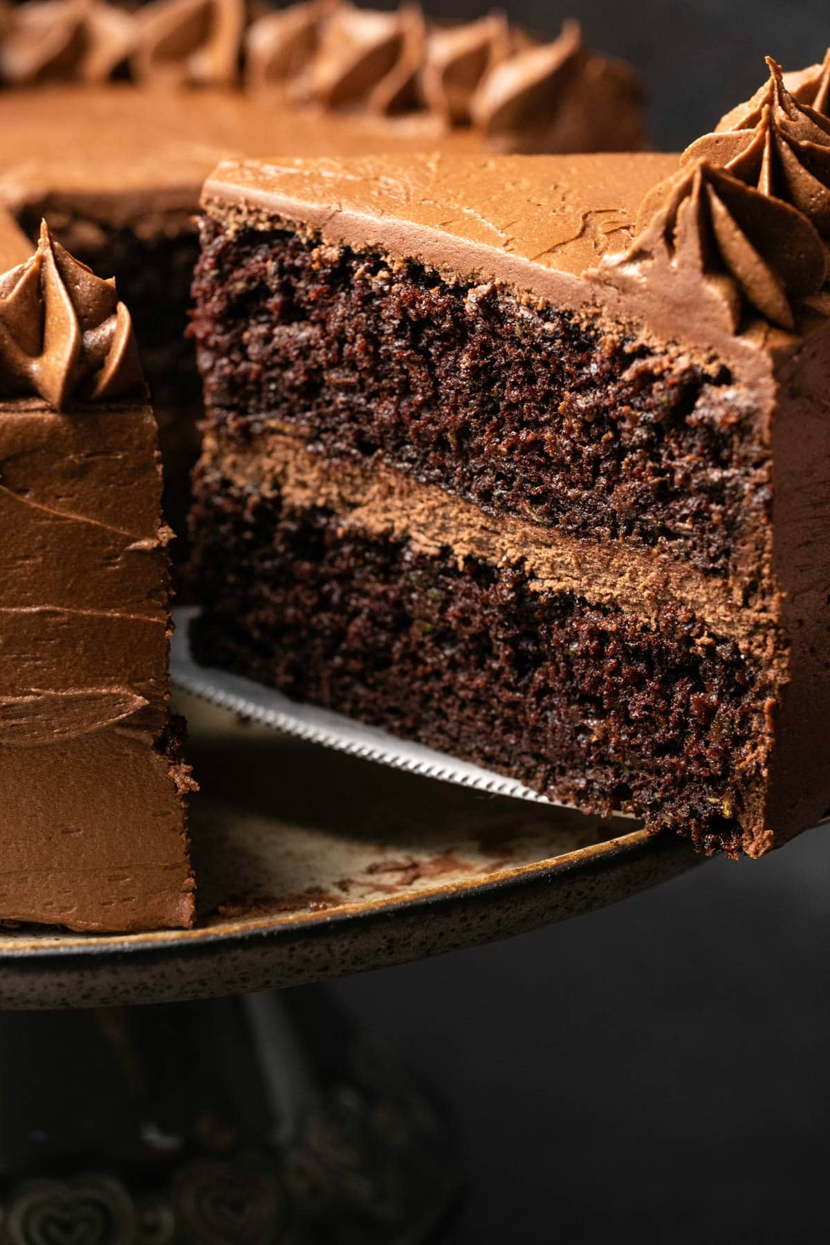 Slice of zucchini chocolate cake on a cake lifter.