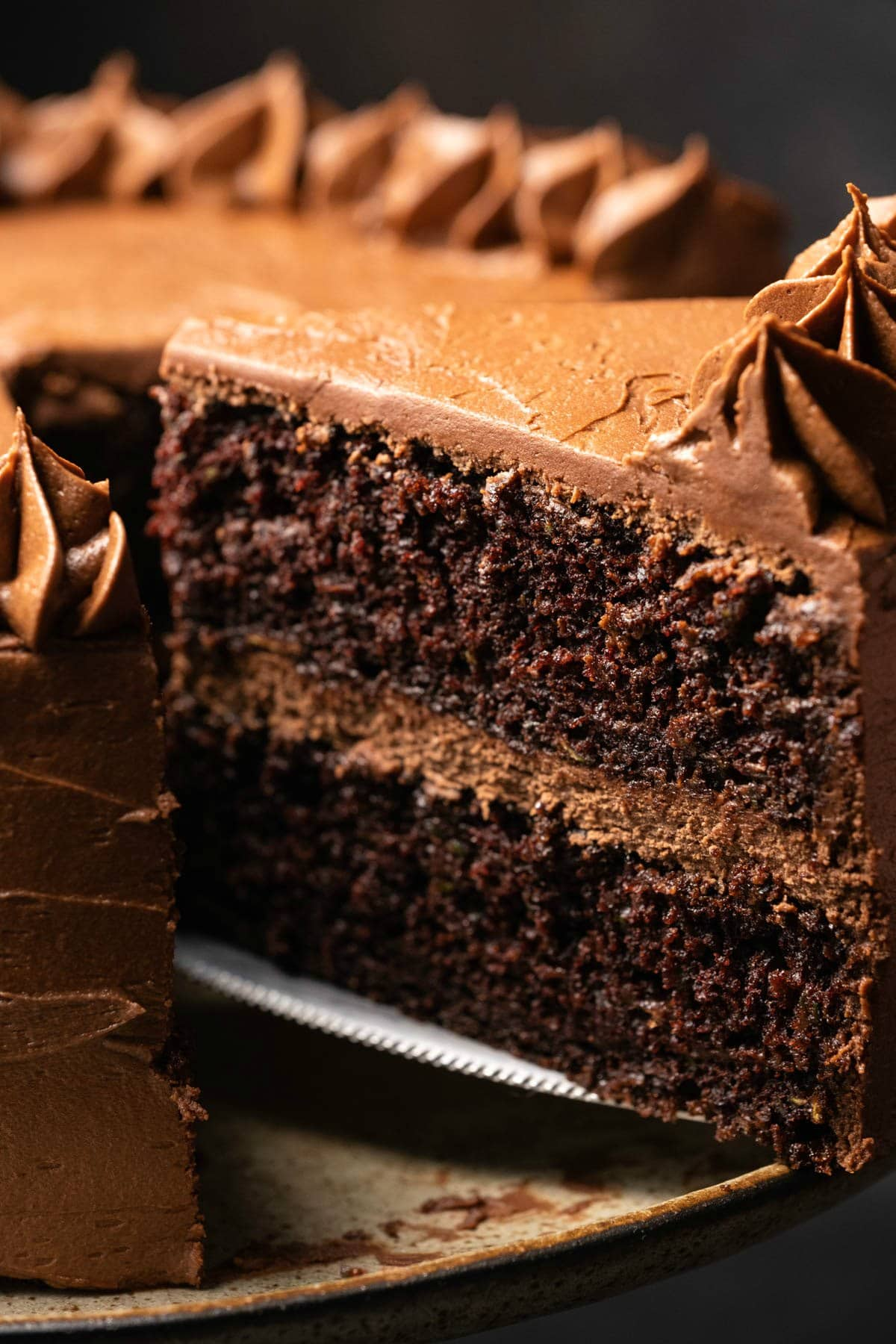 Chocolate zucchini cake on a cake stand with one slice cut and ready to serve.