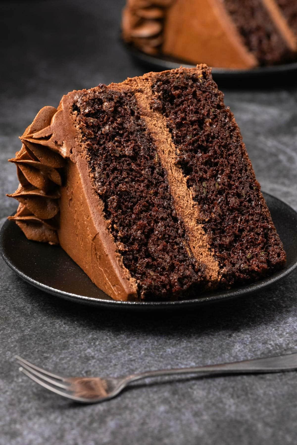 Slice of chocolate zucchini cake on a black plate.