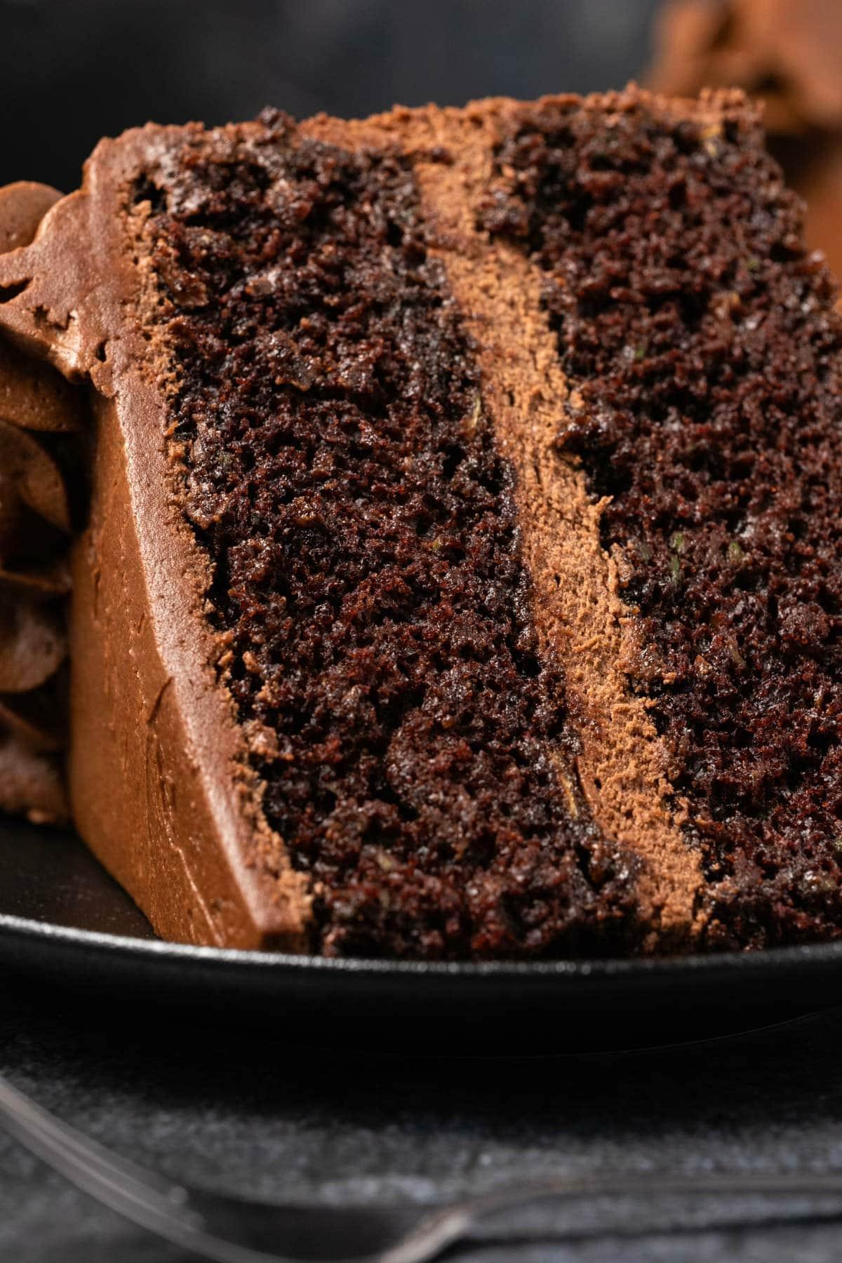 Slice of chocolate cake on a black plate.