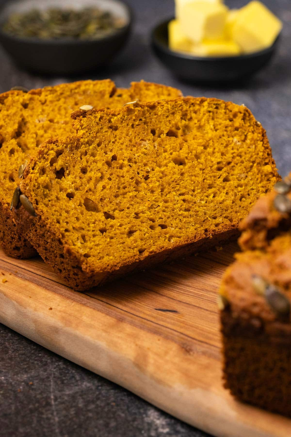 Slices of pumpkin bread on a wooden cutting board.