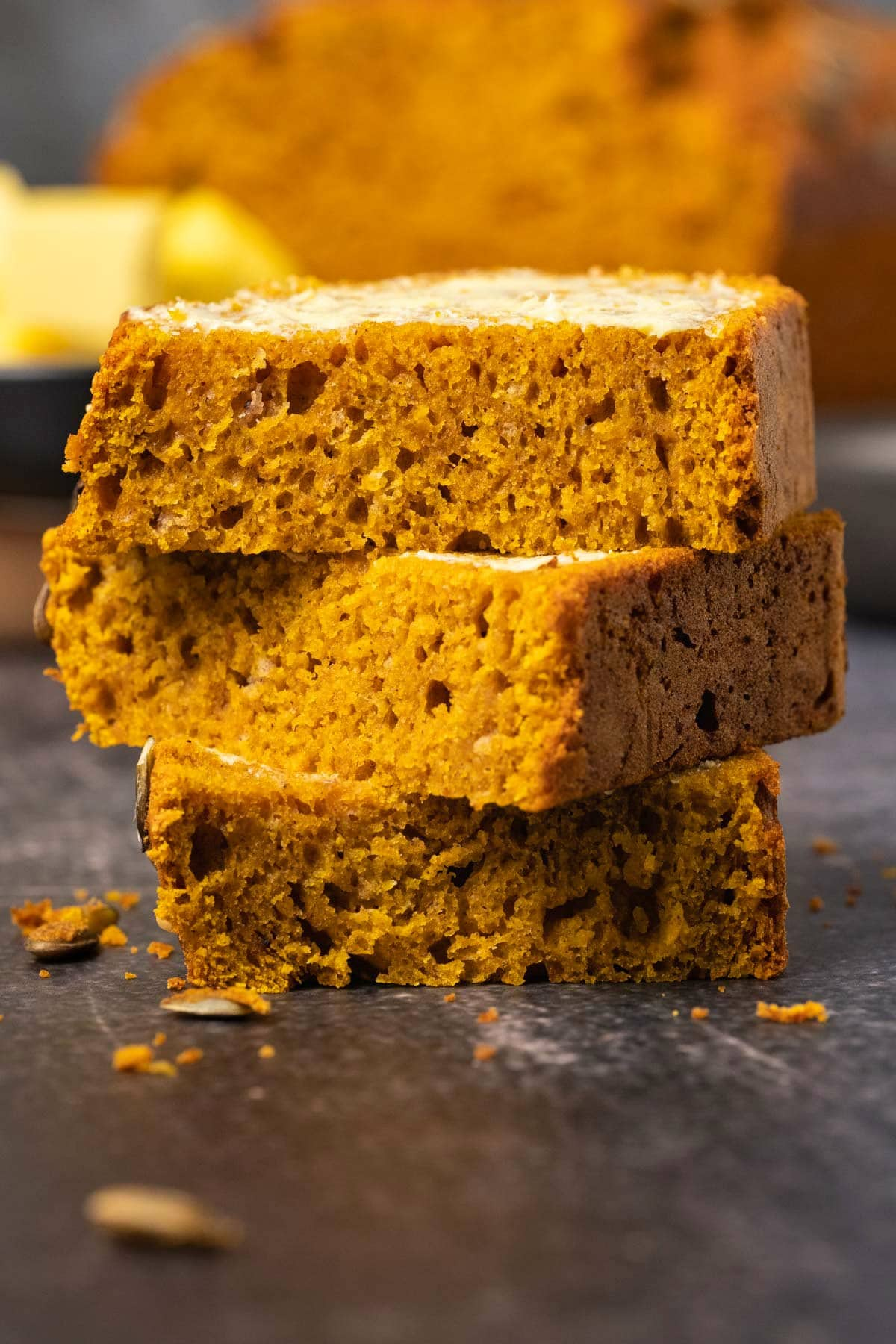 Slices of buttered pumpkin bread in a stack.
