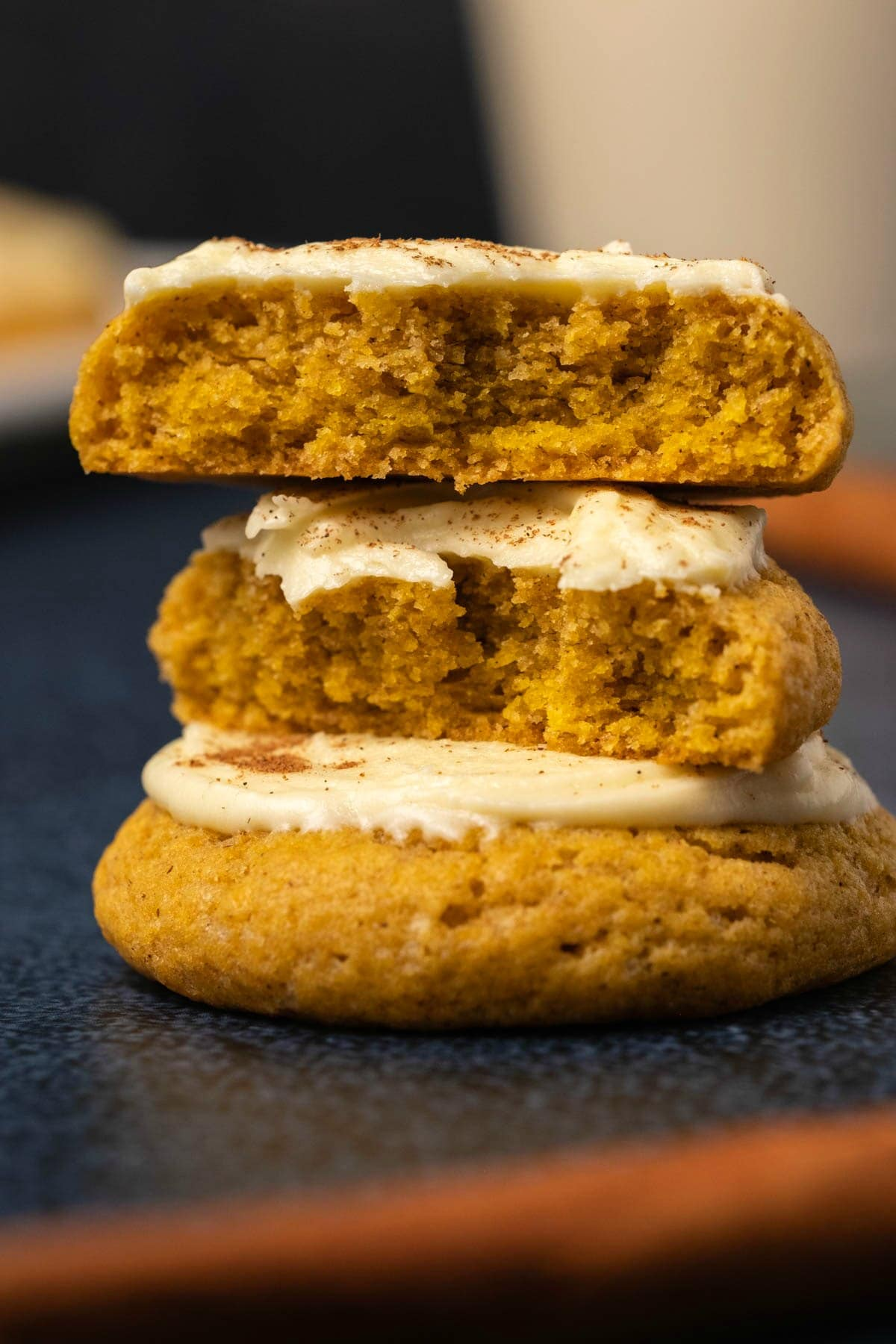 Pumpkin cookies in a stack with the top cookie broken in half to show the center.