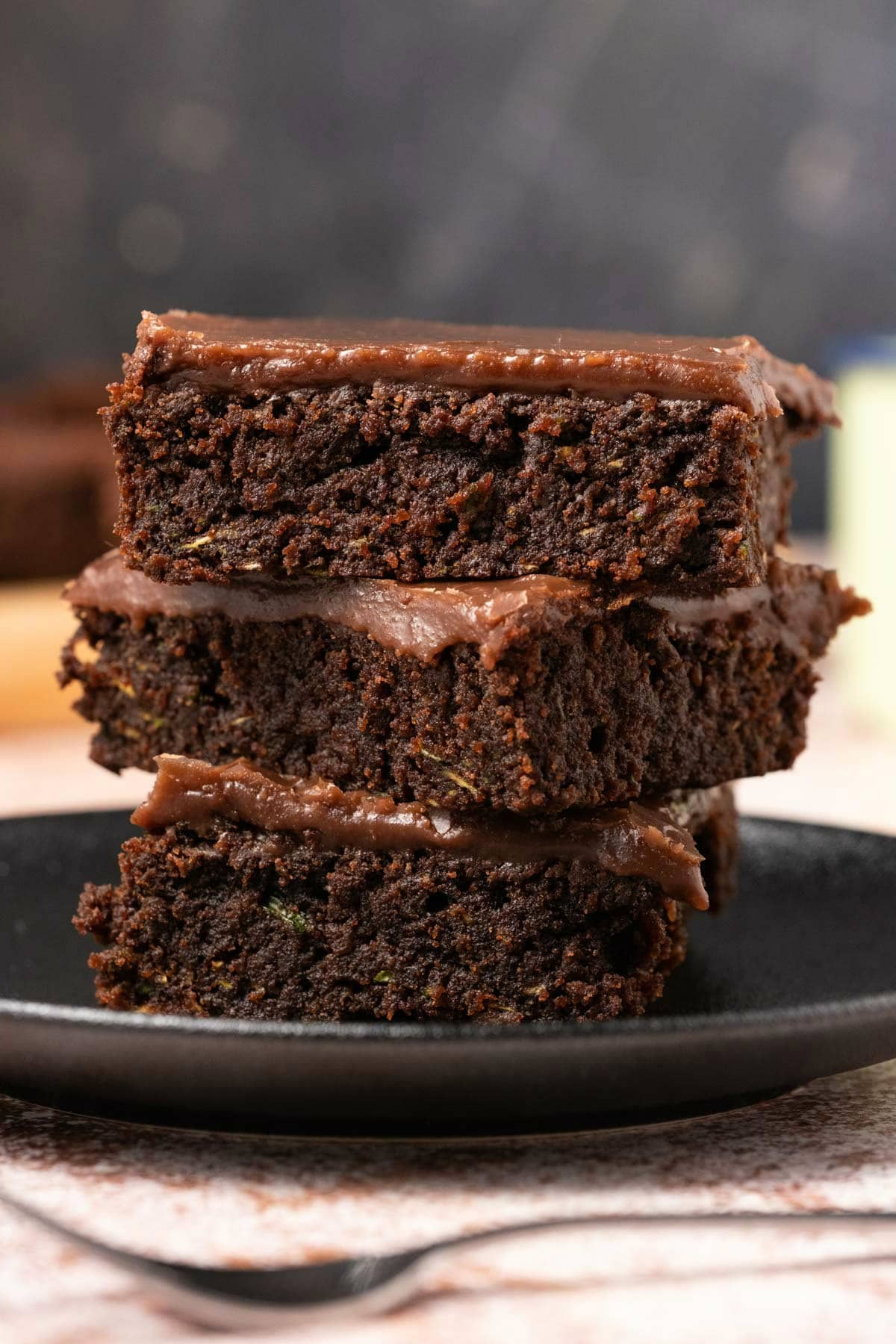 Zucchini brownies stacked up on a black plate.