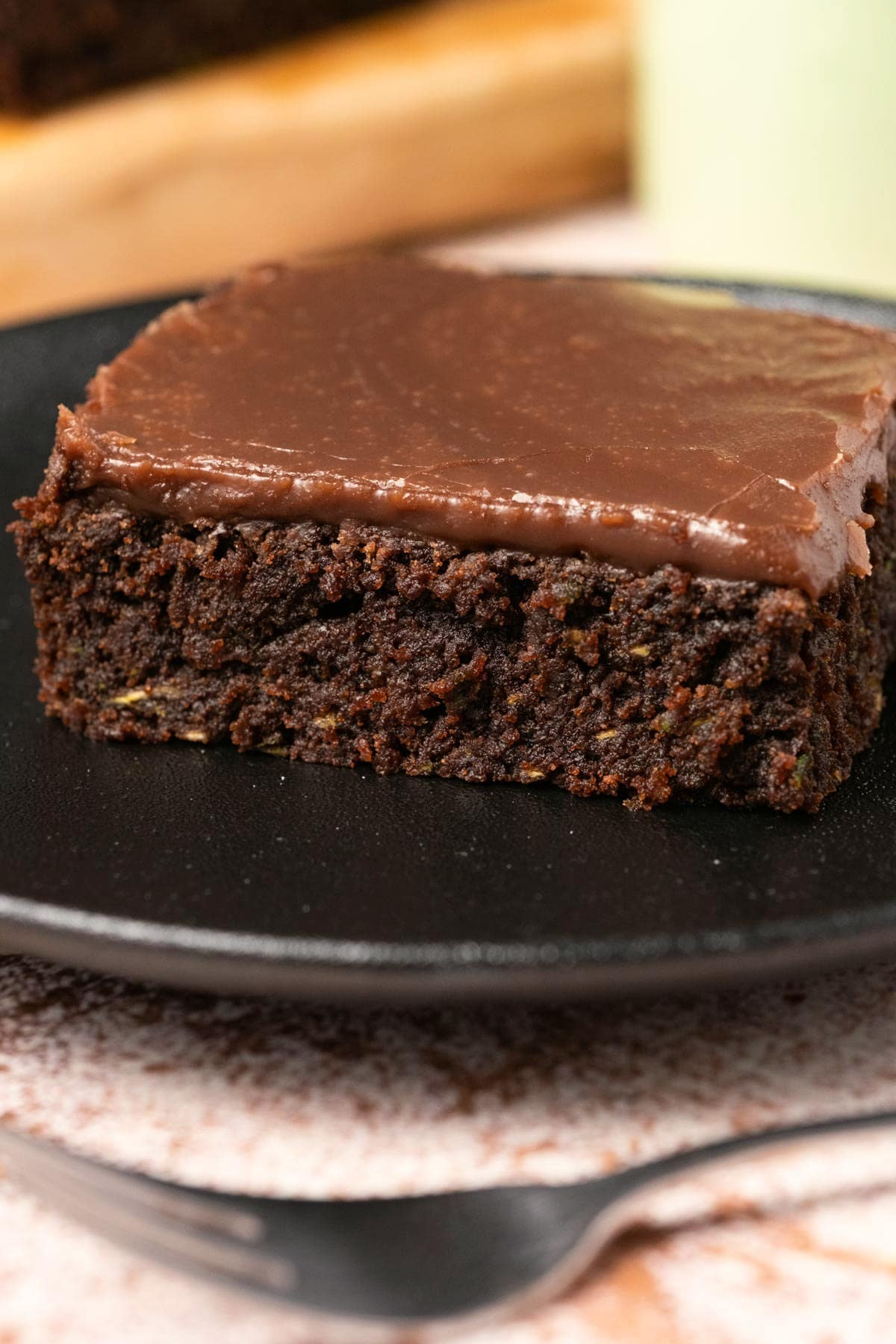 Brownie with chocolate topping on a black plate.