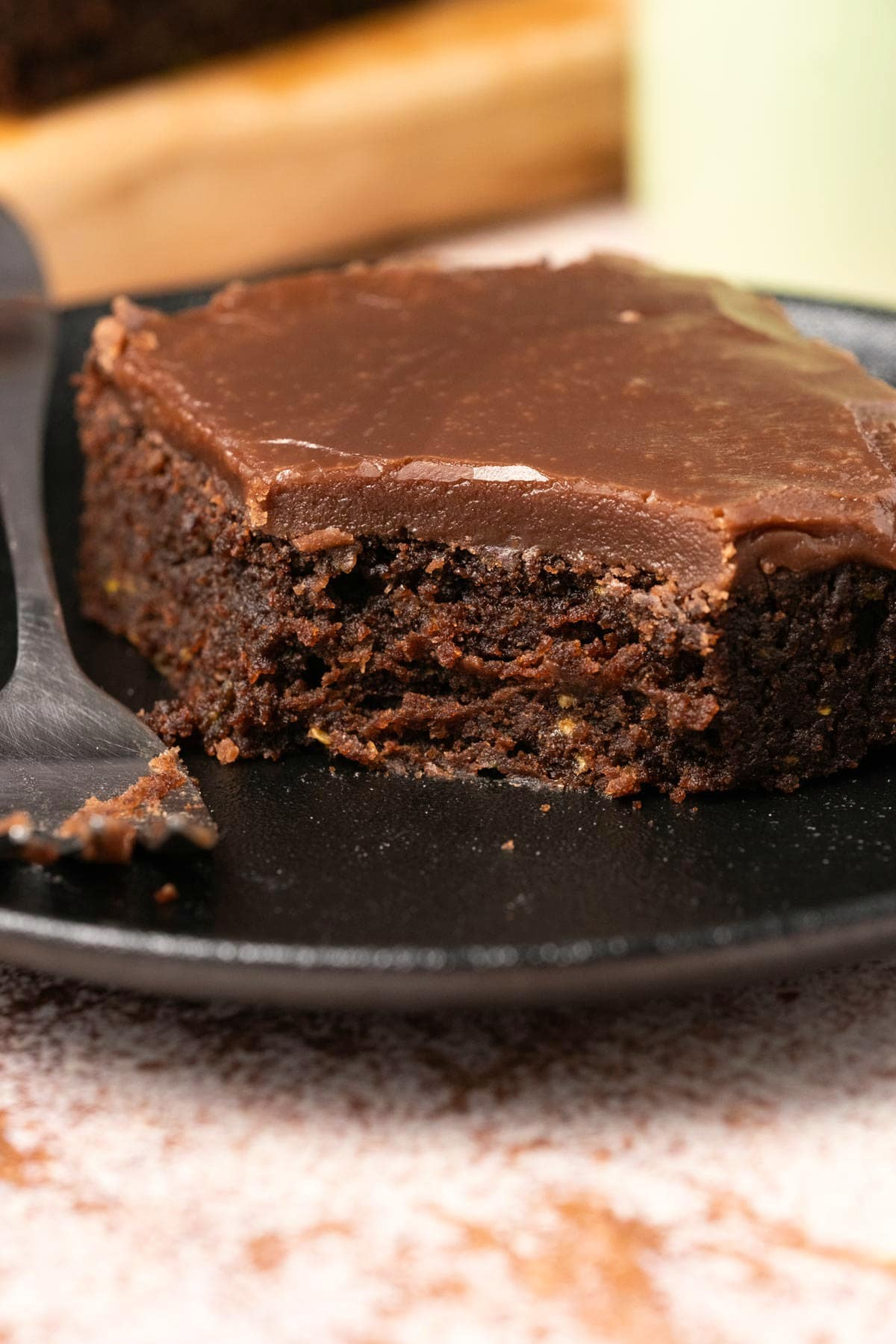 Zucchini brownie on a black plate with a cake fork.
