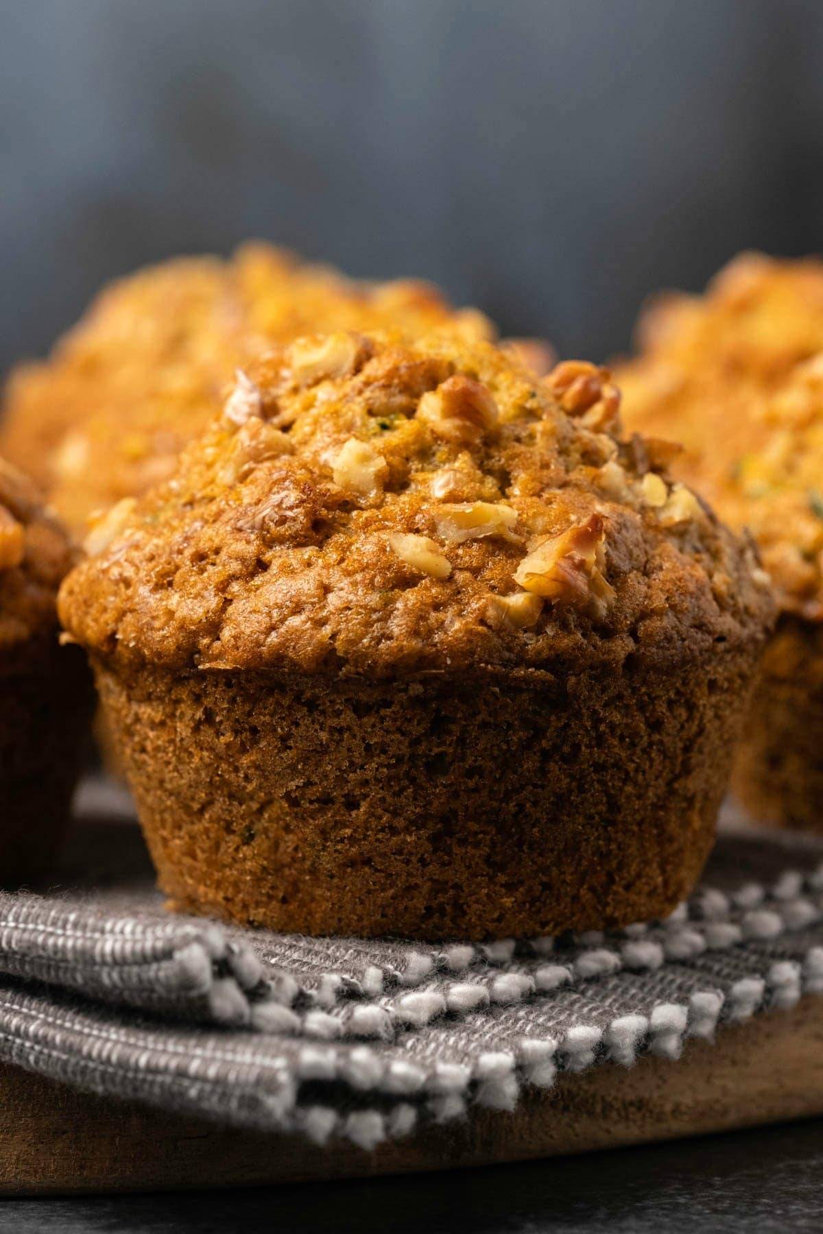 Zucchini muffin on a gray and white cloth.